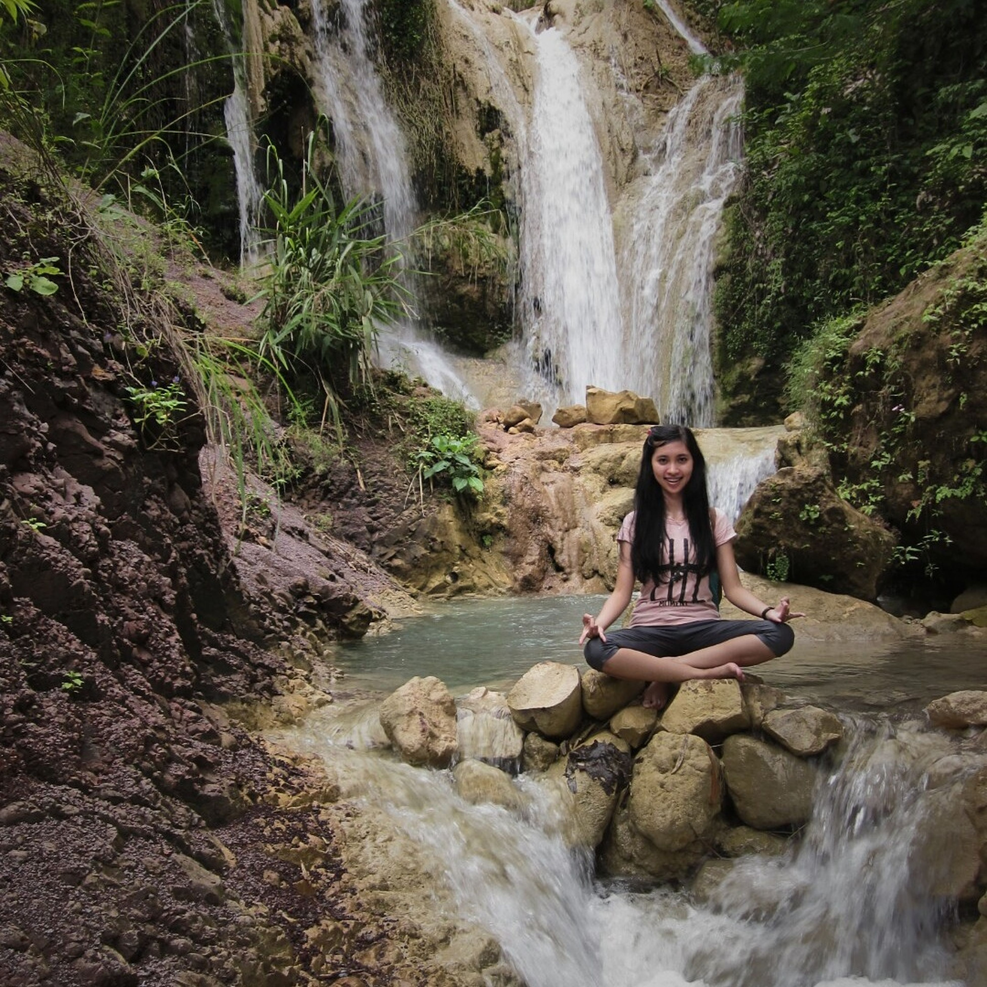 water, lifestyles, leisure activity, rock - object, waterfall, motion, forest, full length, young adult, beauty in nature, nature, vacations, flowing water, tree, scenics, rock, long exposure, rock formation