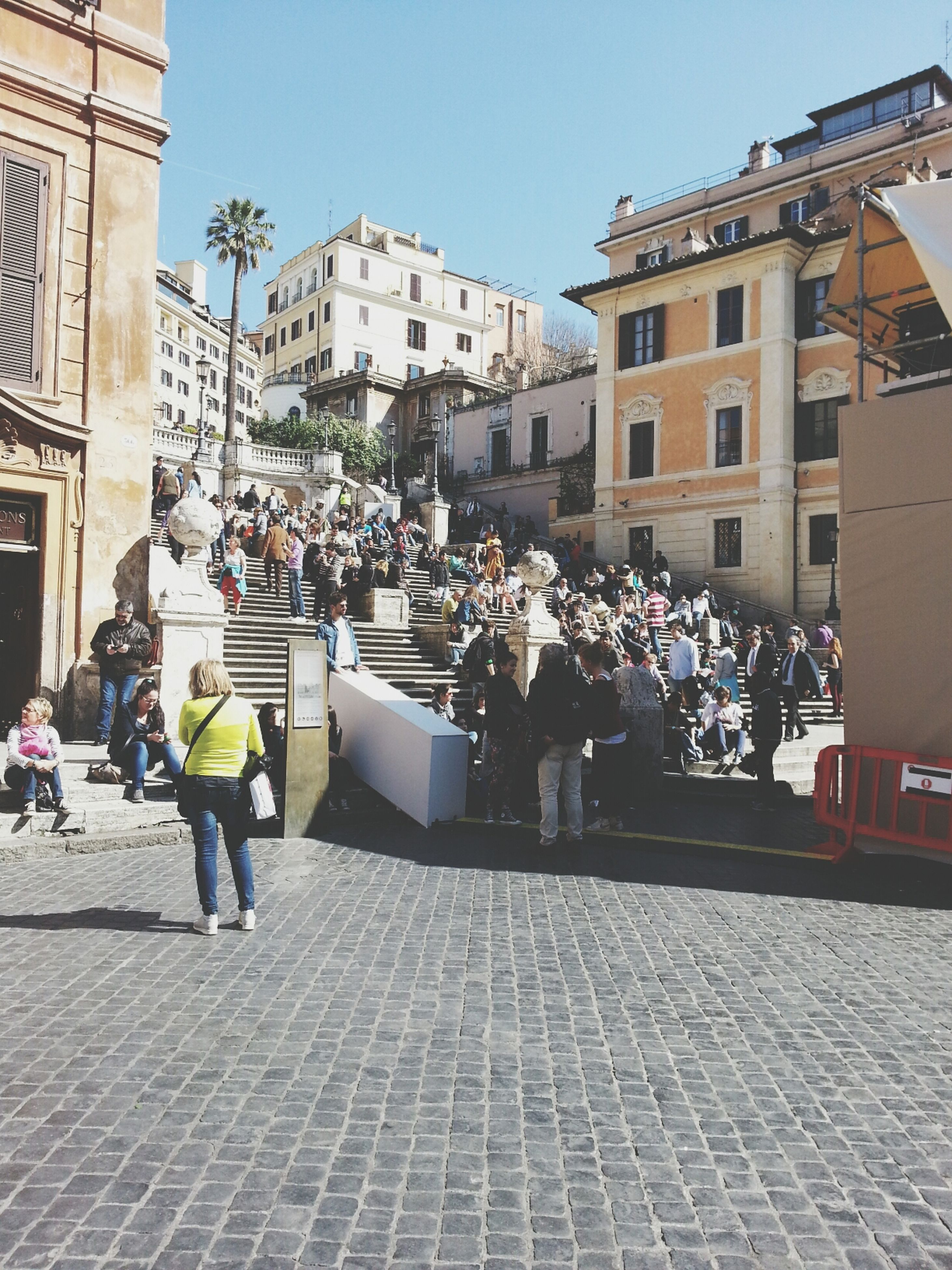 building exterior, architecture, built structure, city, street, large group of people, person, men, city life, walking, lifestyles, building, cobblestone, residential building, sunlight, residential structure, day, leisure activity, outdoors