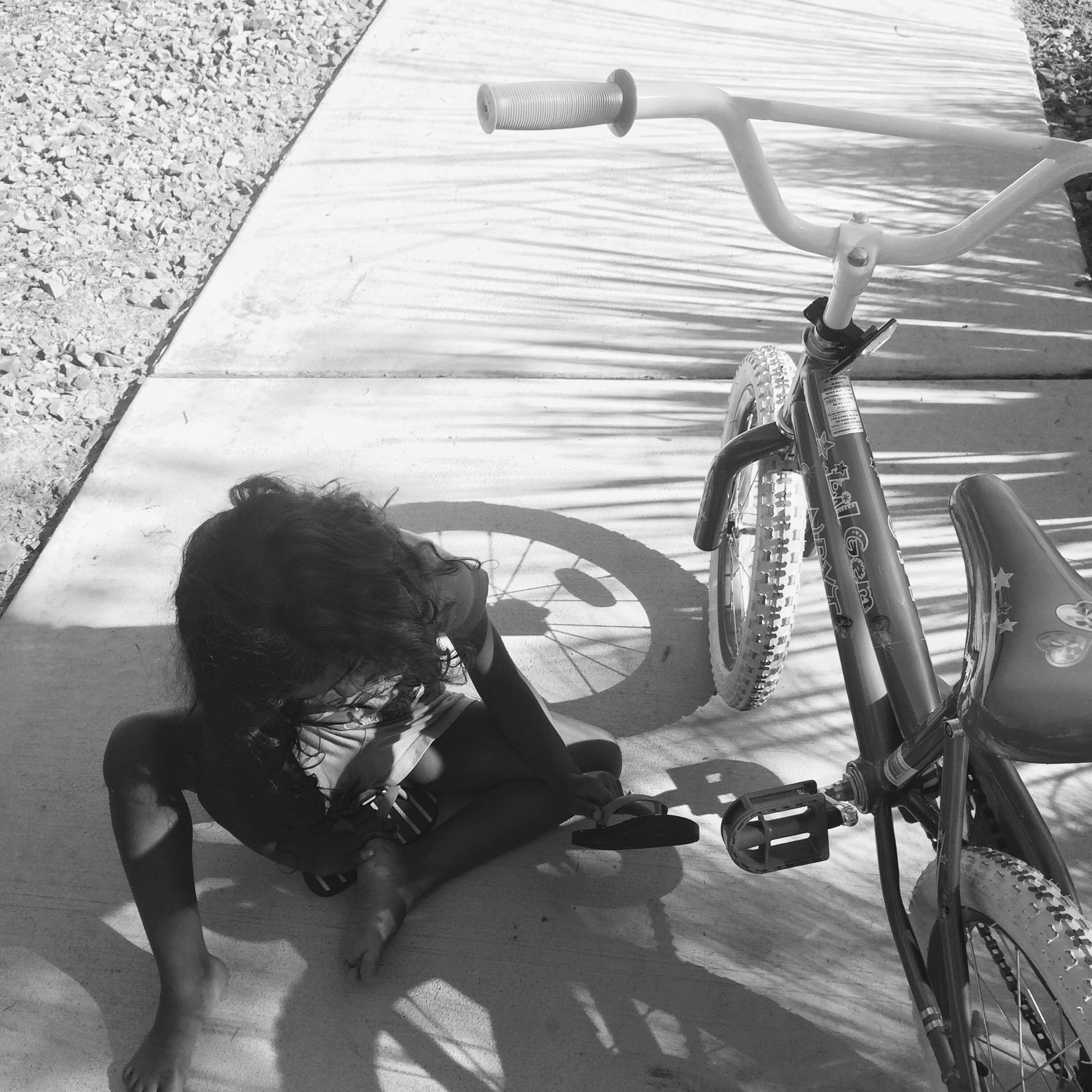 transportation, mode of transport, bicycle, high angle view, land vehicle, shadow, lifestyles, leisure activity, men, sunlight, street, riding, full length, day, travel, sitting, outdoors, person