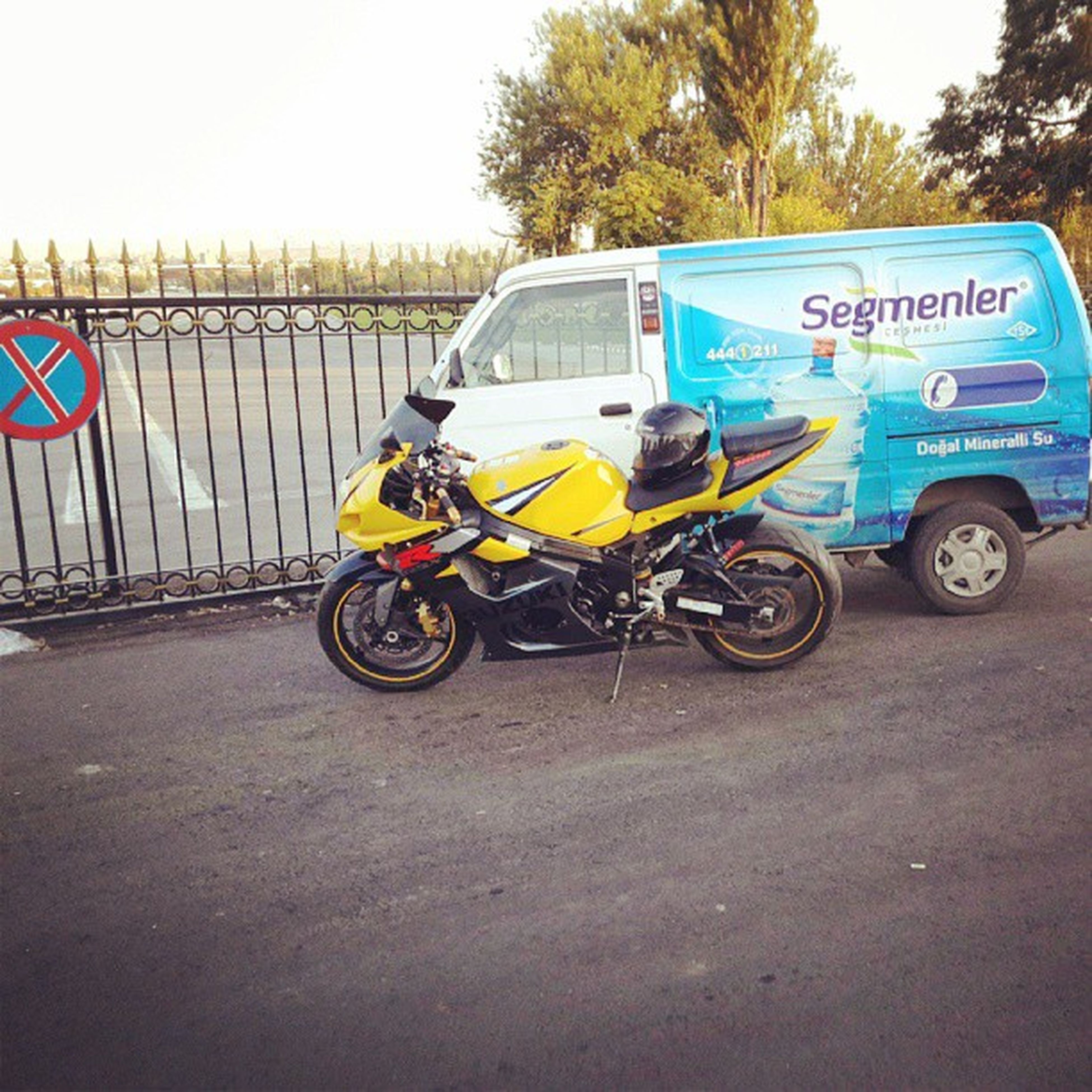 transportation, mode of transport, land vehicle, bicycle, stationary, parked, riding, car, parking, street, travel, road, tree, on the move, day, motorcycle, yellow, cycling, text