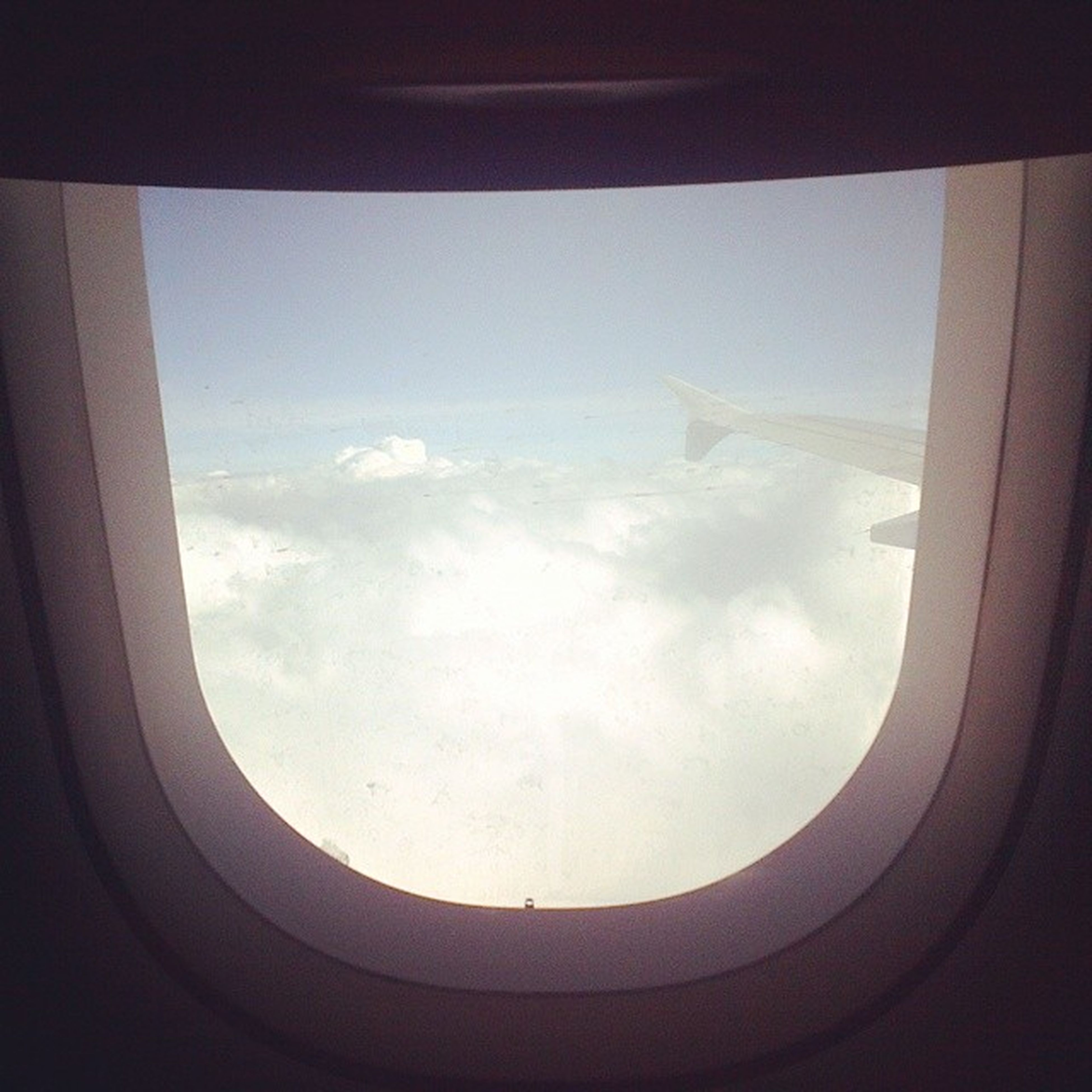 airplane, air vehicle, flying, transportation, aircraft wing, mode of transport, part of, window, aerial view, mid-air, public transportation, sky, cropped, vehicle interior, travel, journey, on the move, transparent, glass - material, cloud - sky