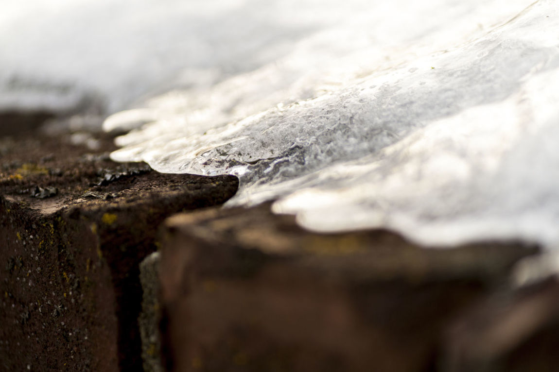 Beauty In Nature Below Zero Brick Wall Close-up Contrast Dark And Light Frozen Ice Masonry Melting Ice Nature Up Close Outdoors Reflective Selective Focus Stark Contrast Unnoticed Art