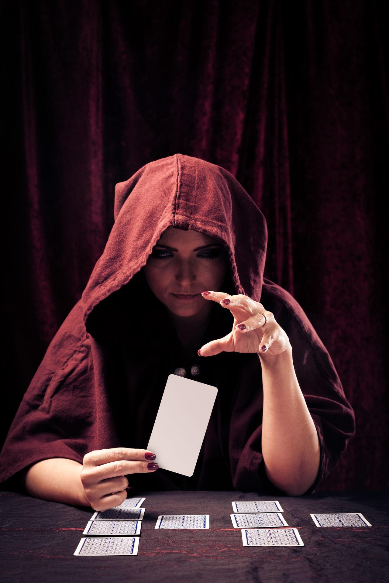 Studio shot of fortune teller. Card Forecast Fortune Teller Fortune Telling Future Magic Paranormal Portrait Psychic Medium Red Spooky Studio Shot Tarot Woman Women Young Women