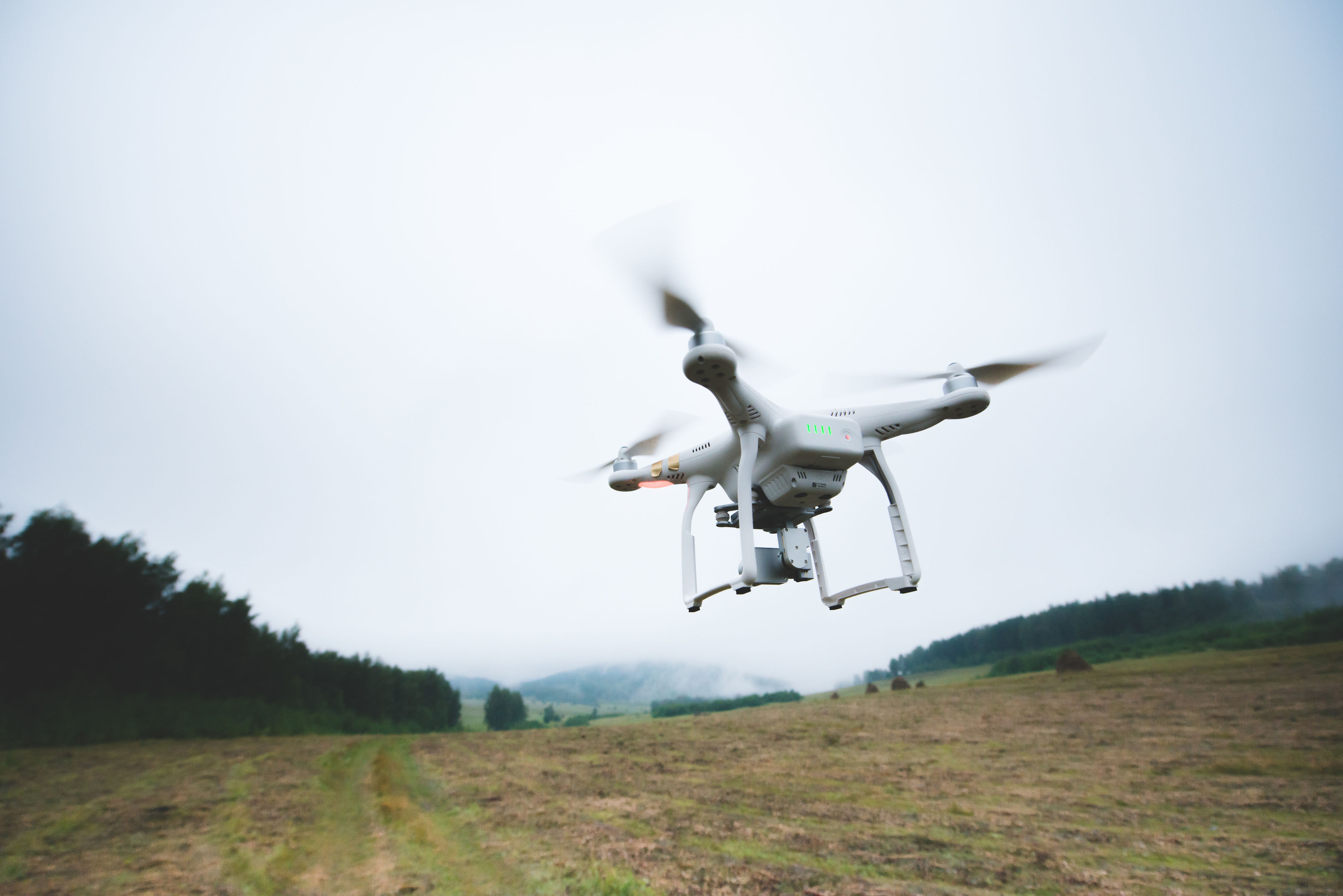 flying, mid-air, field, grass, air vehicle, outdoors, airplane, no people, nature, day, sky, drone