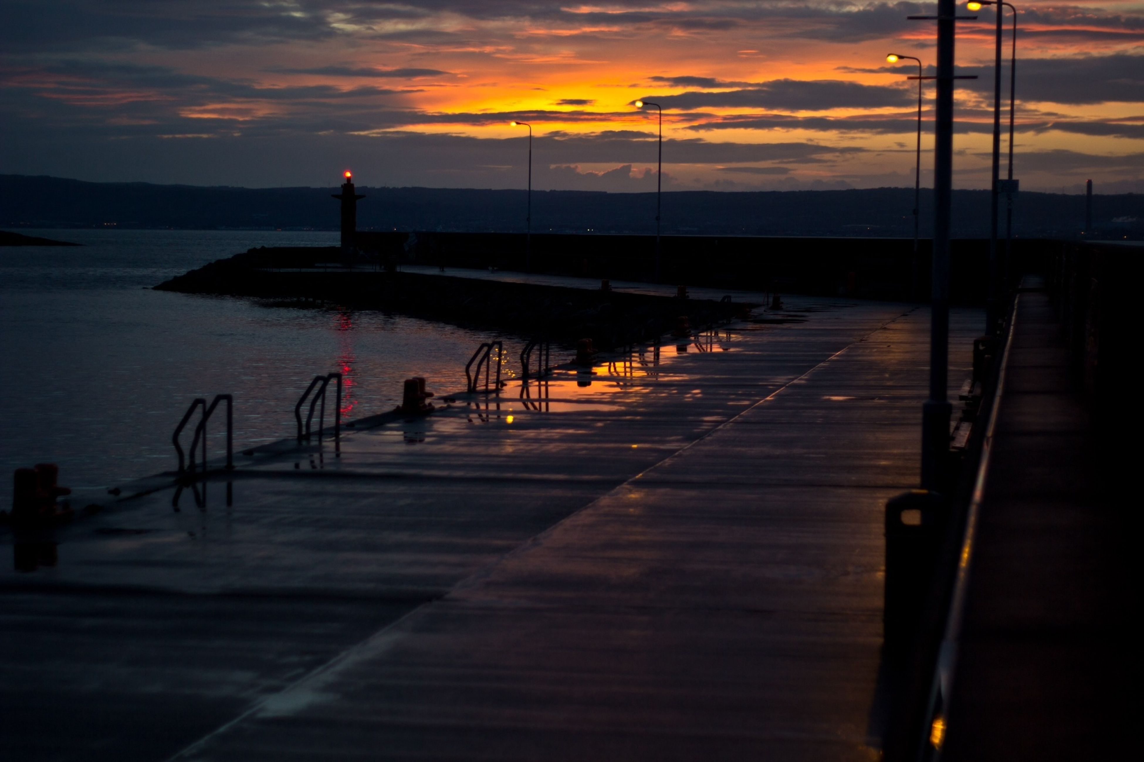 sunset, water, sky, pier, orange color, scenics, tranquil scene, sea, tranquility, beauty in nature, cloud - sky, silhouette, idyllic, nature, the way forward, empty, railing, street light, jetty, lake