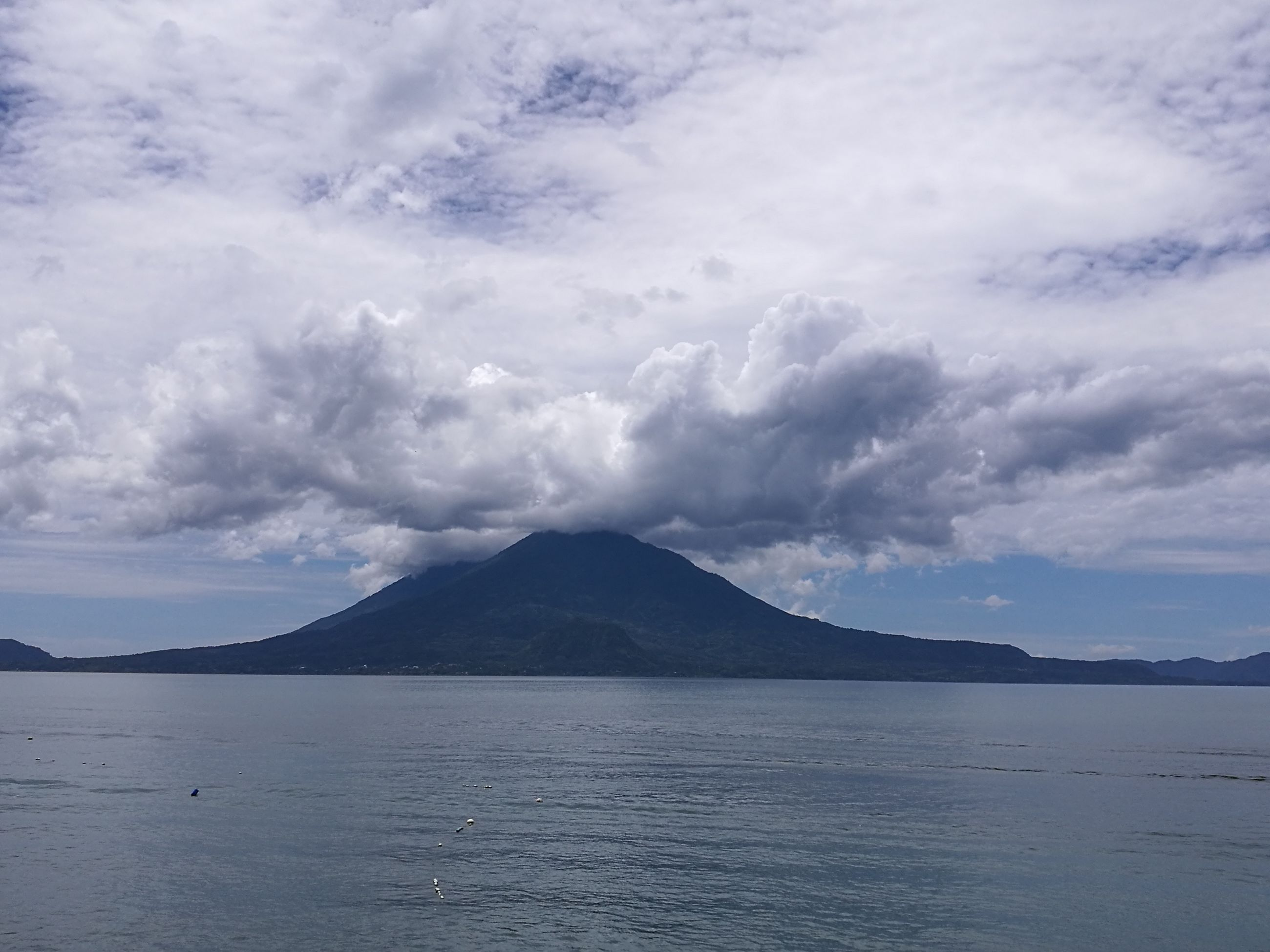 mountain, water, tranquil scene, scenics, tranquility, sea, beauty in nature, waterfront, sky, nature, idyllic, cloud - sky, majestic, non-urban scene, calm, tourism, travel destinations, mountain range, remote, cloud, outdoors, day, cloudscape, vacations, seascape, atmospheric mood, dramatic sky, solitude, cumulus cloud, coastline, cloudy, ocean, atmosphere, no people