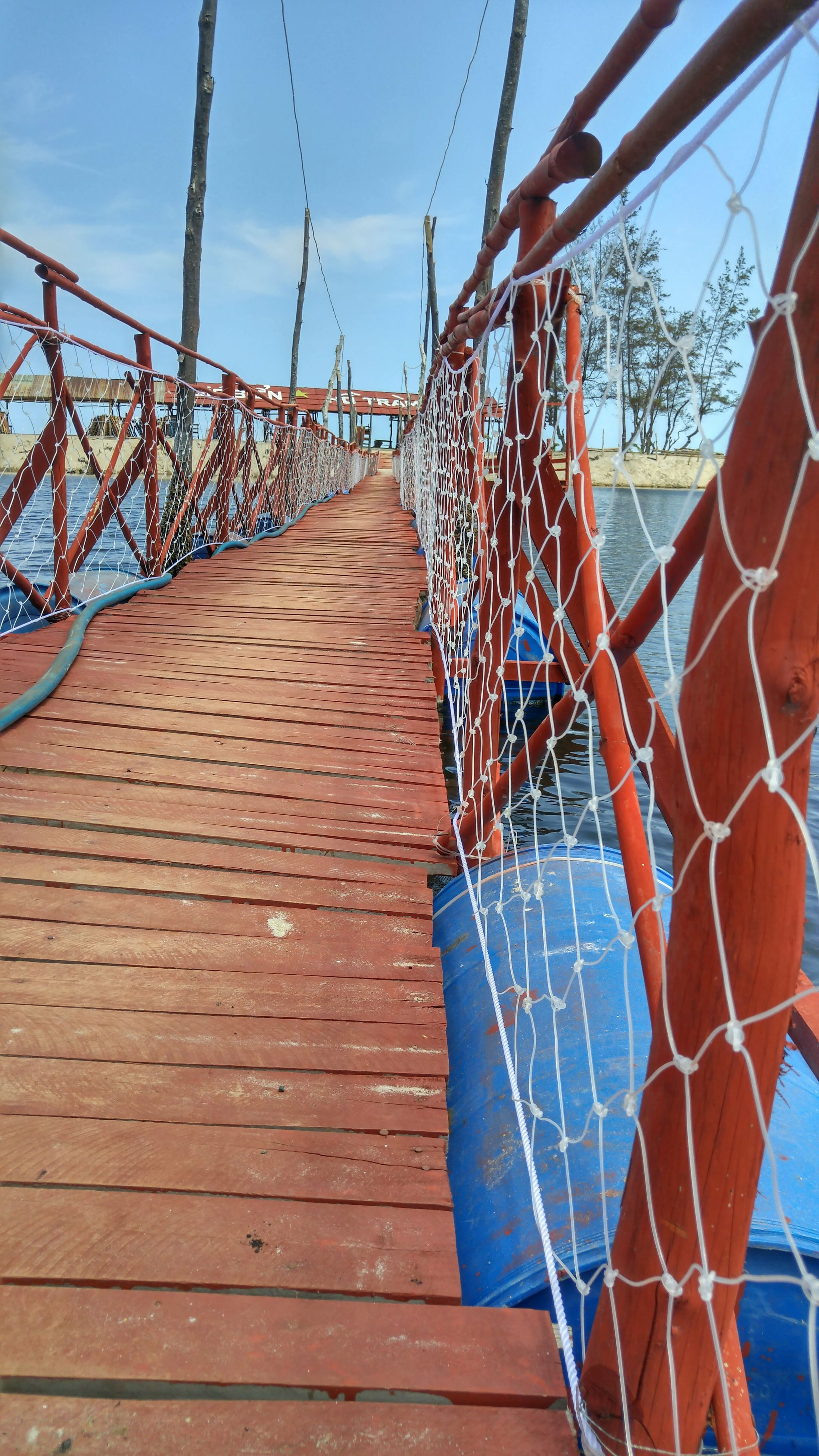 built structure, architecture, low angle view, metal, sky, building exterior, blue, connection, metallic, day, outdoors, chainlink fence, grid, sunlight, no people, pattern, diminishing perspective, clear sky, railing, protection