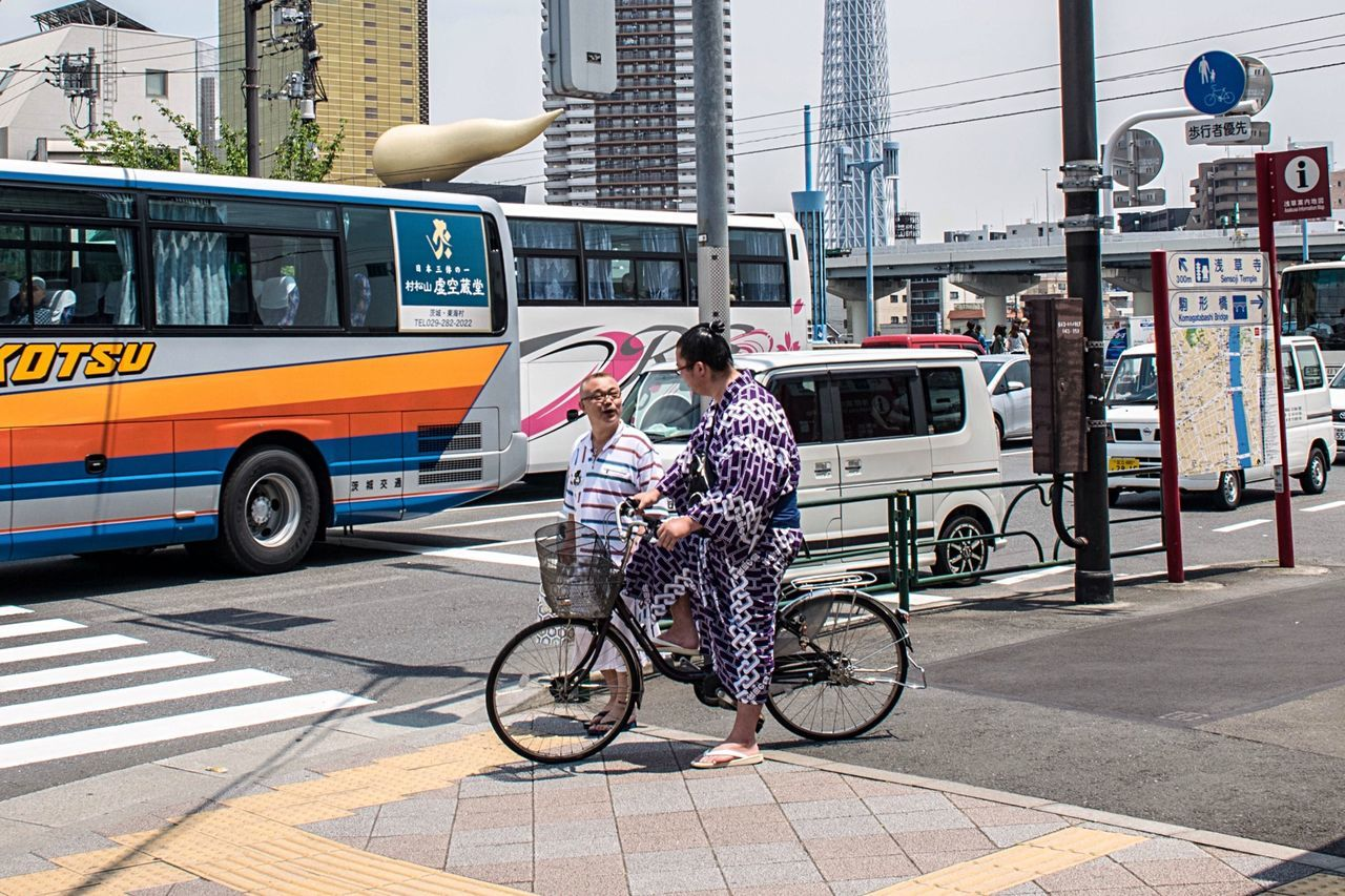 transportation, mode of transport, city, bicycle, city life, land vehicle, city street, public transportation, street, bus, car, day, full length, outdoors, building exterior, only women, one woman only, adult, one person, people, adults only, architecture, one young woman only, young adult