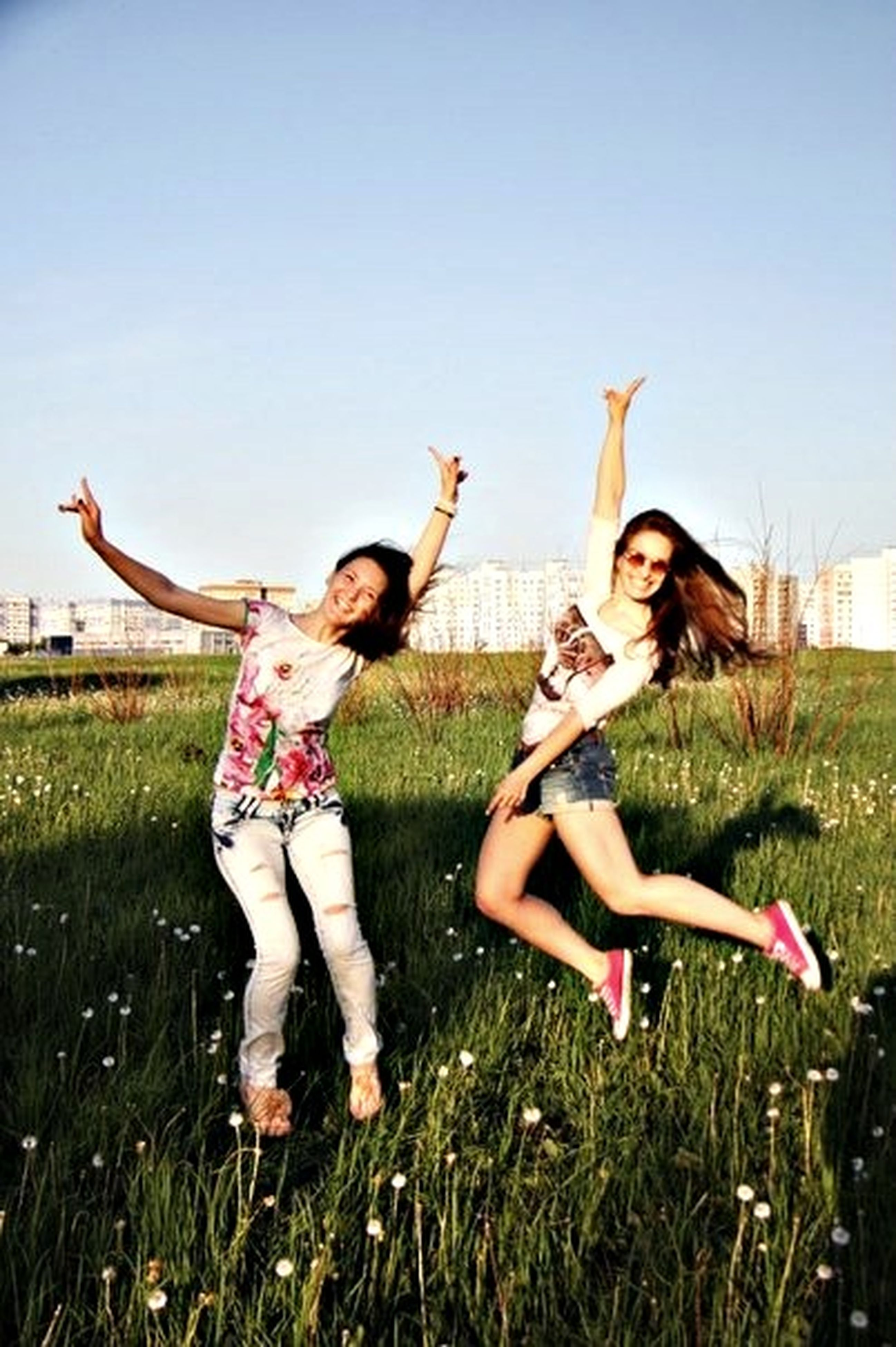 lifestyles, leisure activity, grass, full length, young adult, person, casual clothing, young women, childhood, enjoyment, fun, happiness, field, girls, elementary age, togetherness, arms raised, playing