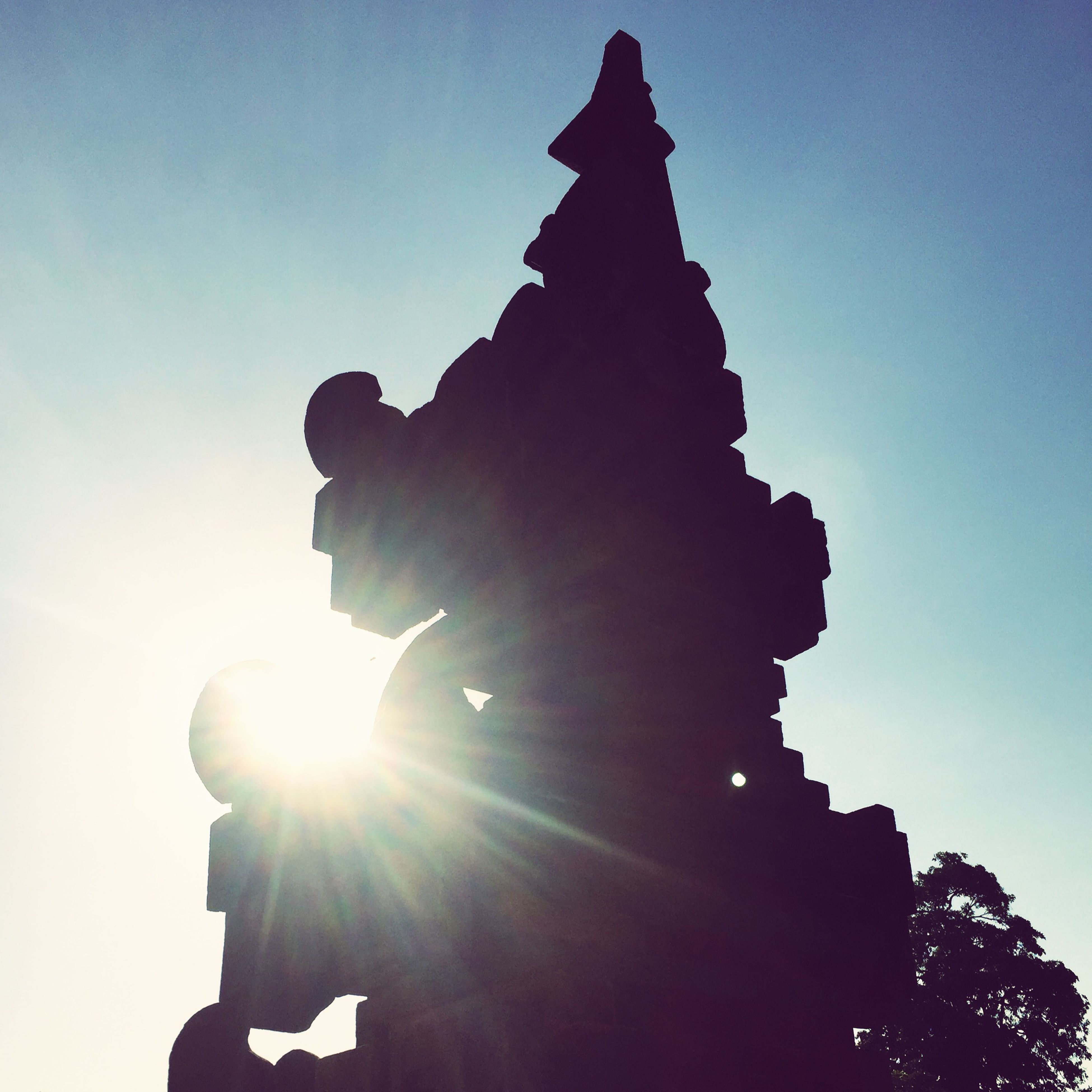 low angle view, sun, sunbeam, clear sky, silhouette, sunlight, lens flare, built structure, architecture, sky, building exterior, religion, spirituality, history, statue, place of worship, sculpture, blue, sunny, outdoors
