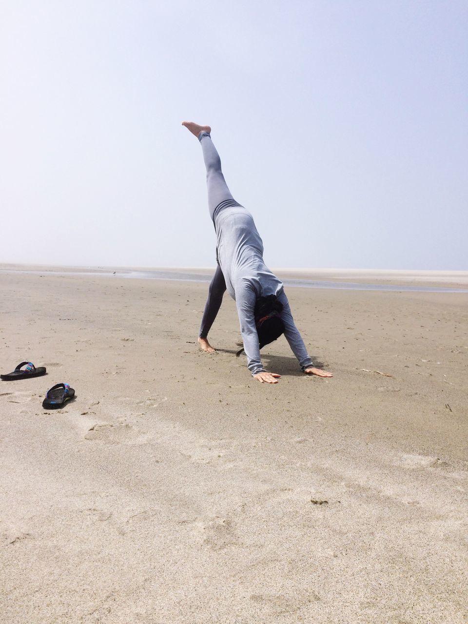 Woman Doing Handstand On Beach Against Clear Sky