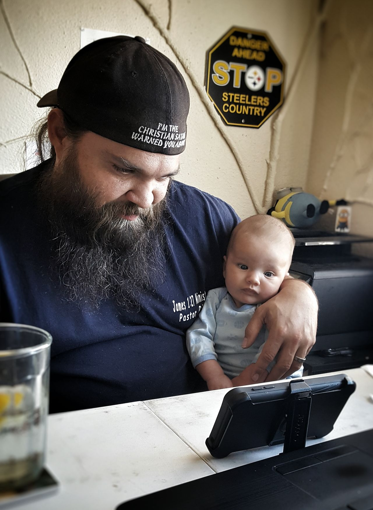 Baby Two People Indoors  People Adult Day Technology Baby Boy Father Fatherhood Moments Watching Steelers Steelers Pride  Home Office Christian Christianity Hat Beard Bonding Sitting Holding Phone