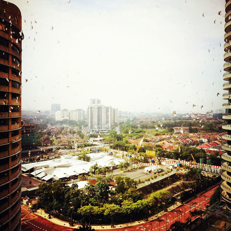 Looking out of the hotel window Cityscape City Building Exterior Sky Architecture Rain Outdoors Skyscraper No People Water Built Structure Urban Skyline Tree Day Close-up Damansara Petaling Jaya Hotel Room Raindrops On My Window Highrise Rainy Day Malaysia Grey Sky Window Apres La Pluie....