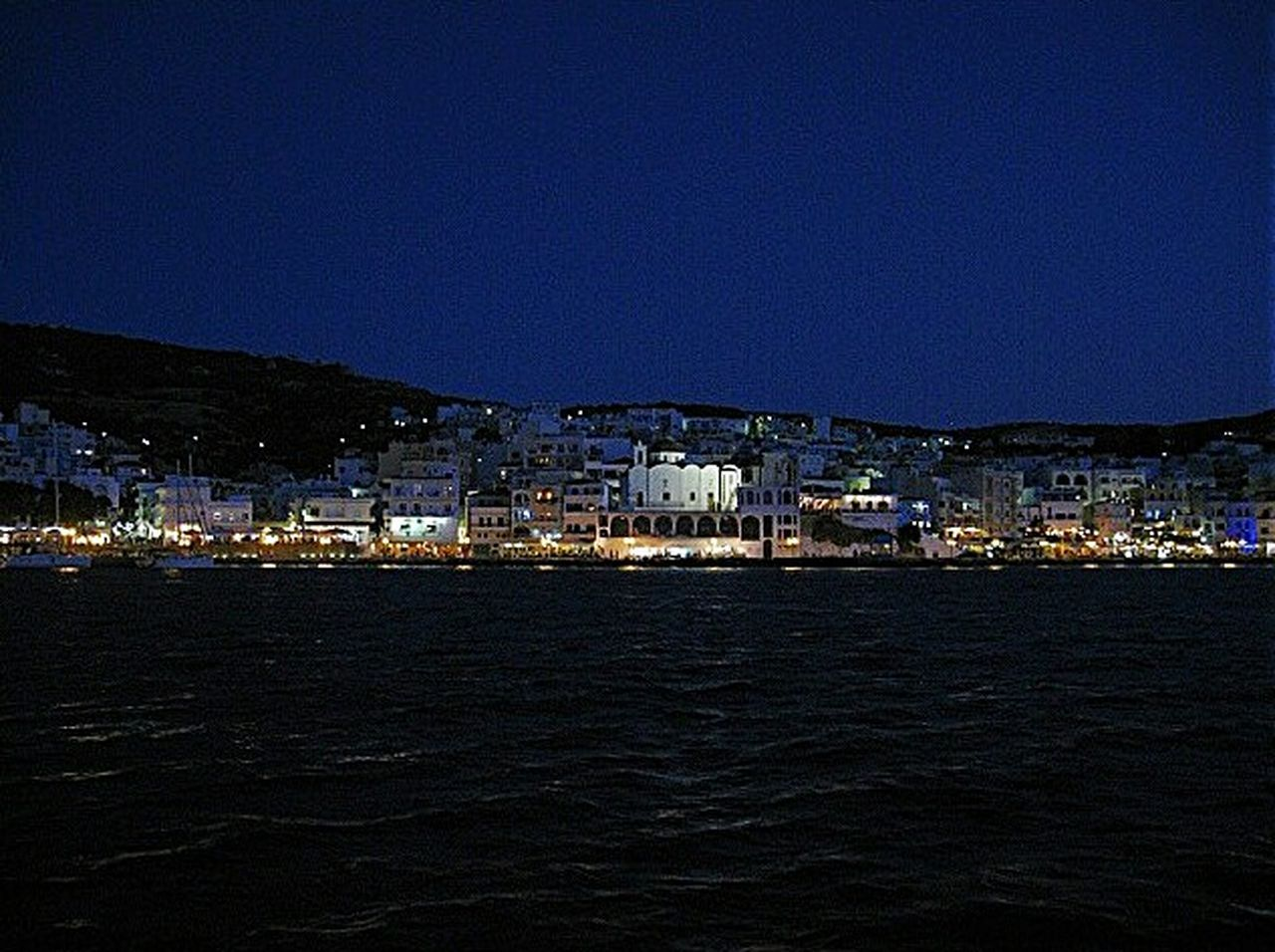 architecture, night, building exterior, cityscape, city, built structure, no people, outdoors, residential building, sea, water, house, waterfront, sky, town, illuminated, travel destinations, nature, clear sky, sailboat, view into land, mountain, urban skyline, mast, yacht