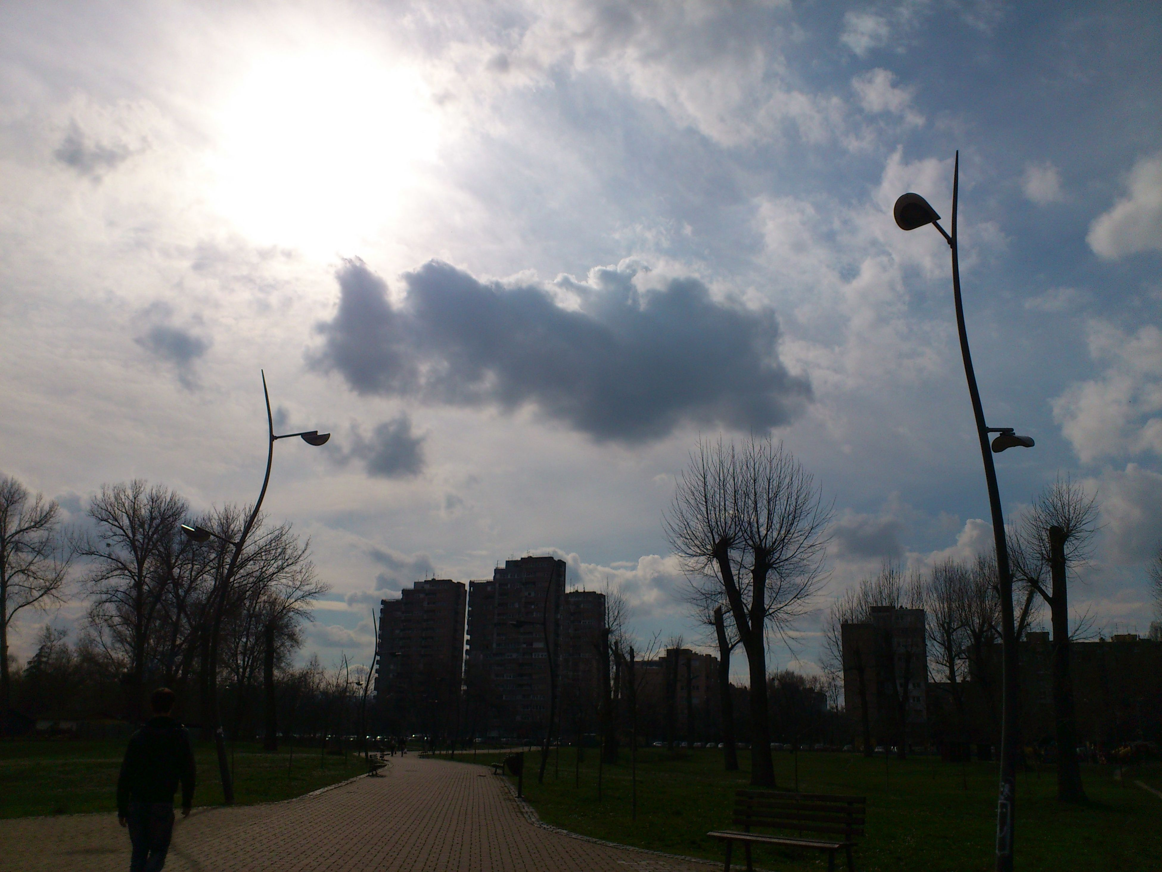 building exterior, sky, architecture, built structure, cloud - sky, street light, tree, city, silhouette, cloud, sunlight, street, sun, men, cloudy, bare tree, lifestyles, road, incidental people