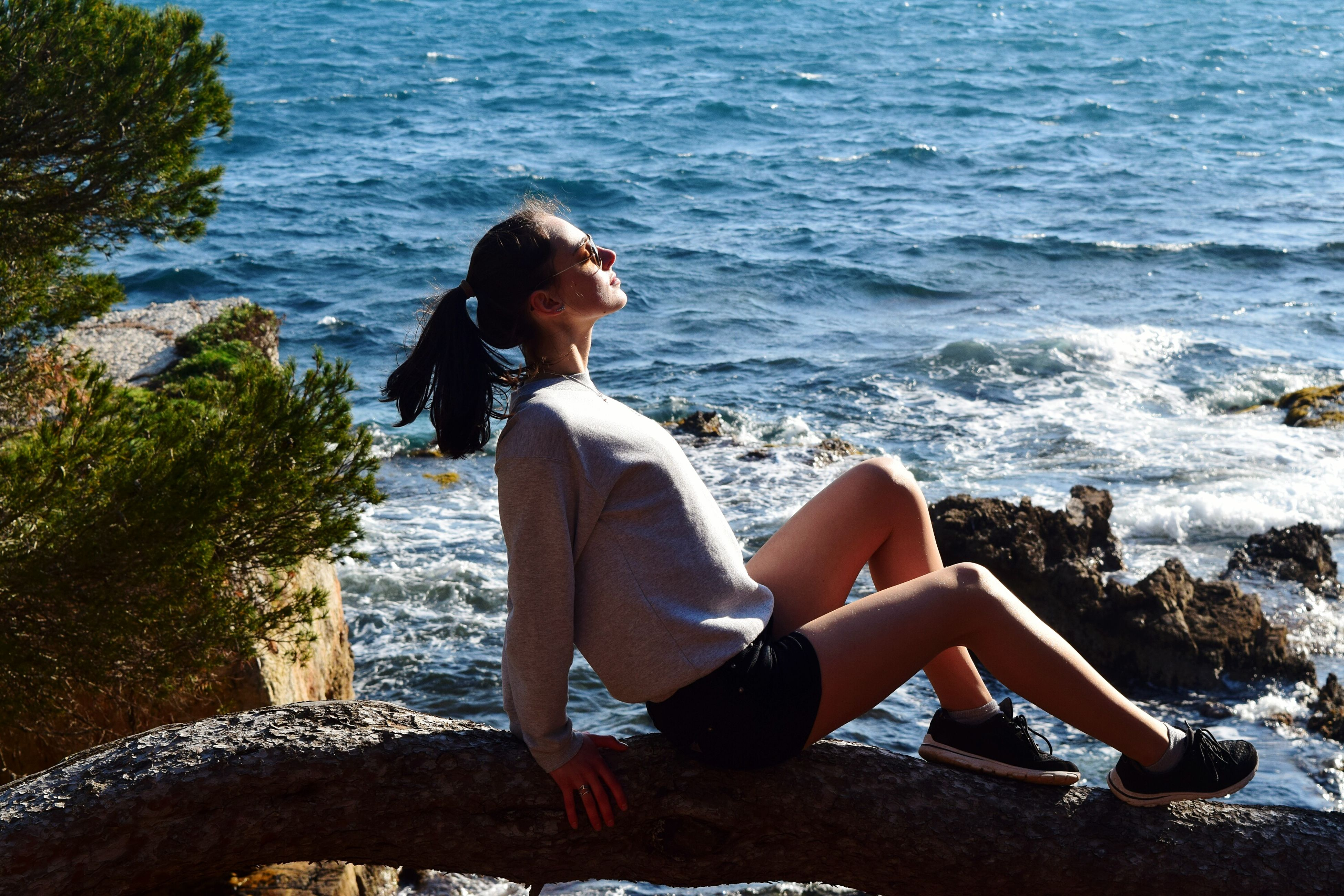 sunlight, sitting, sea, water, summer, leisure activity, relaxation, lifestyles, day, full length, one person, beach, one woman only, outdoors, vacations, only women, nature, young adult, one young woman only, adults only, young women, beauty in nature, people, adult
