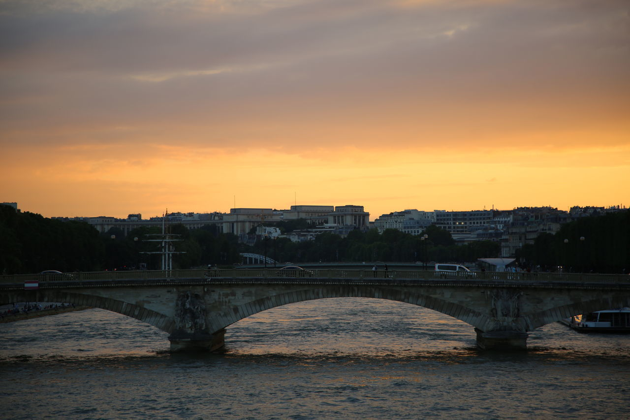 bridge - man made structure, connection, sunset, architecture, river, built structure, water, sky, building exterior, city, transportation, bridge, cloud - sky, outdoors, no people, tree, travel destinations, cityscape, nature, chain bridge, day