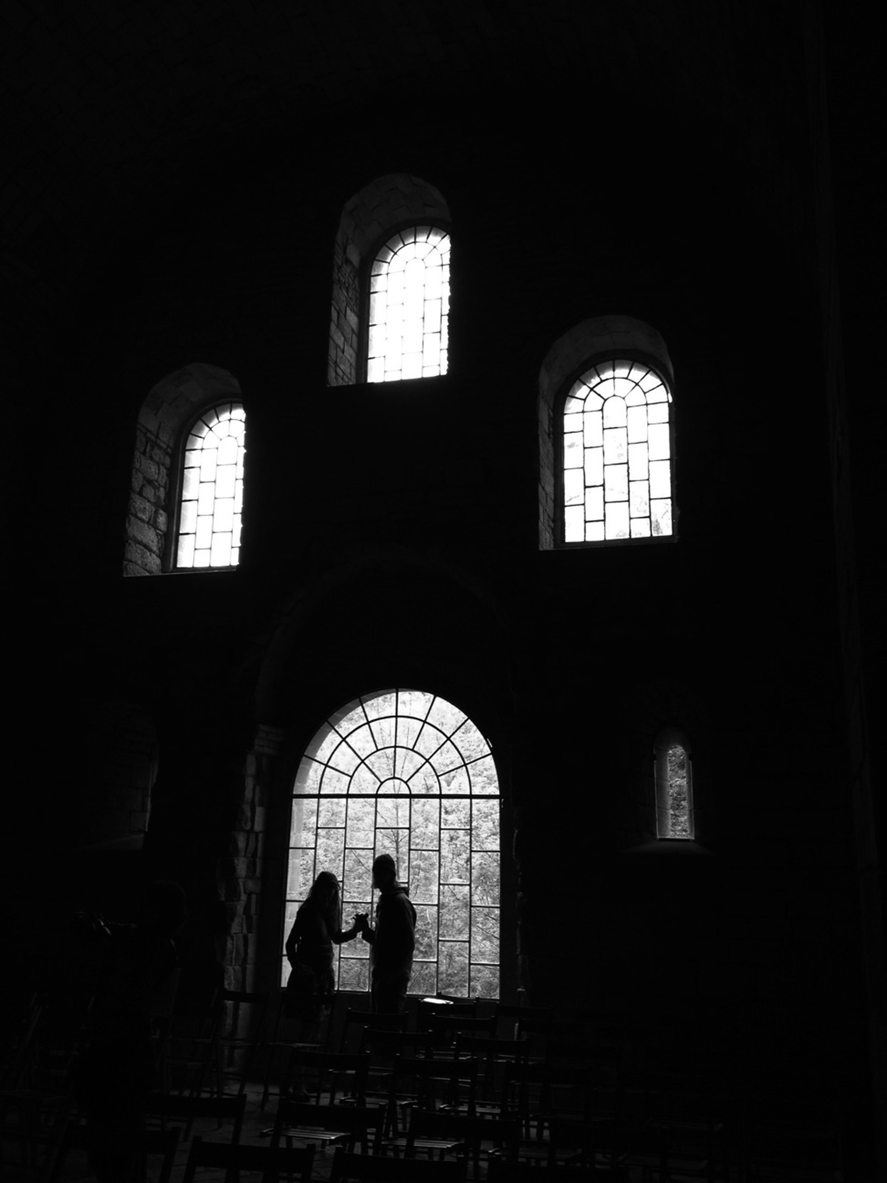 arch, indoors, window, architecture, silhouette, built structure, lifestyles, men, dark, leisure activity, person, standing, entrance, full length, unrecognizable person, archway, rear view