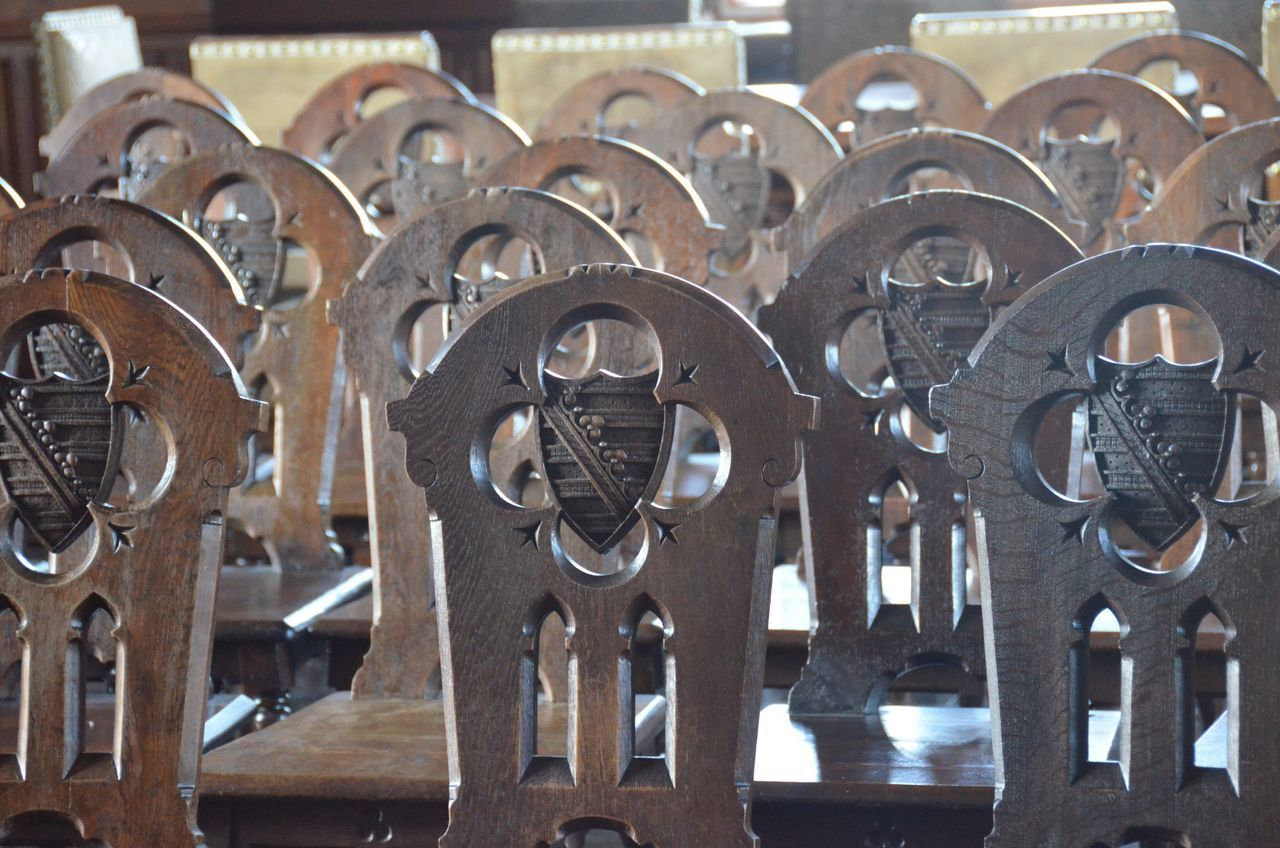 Empty Wooden Chairs Arranged In Room