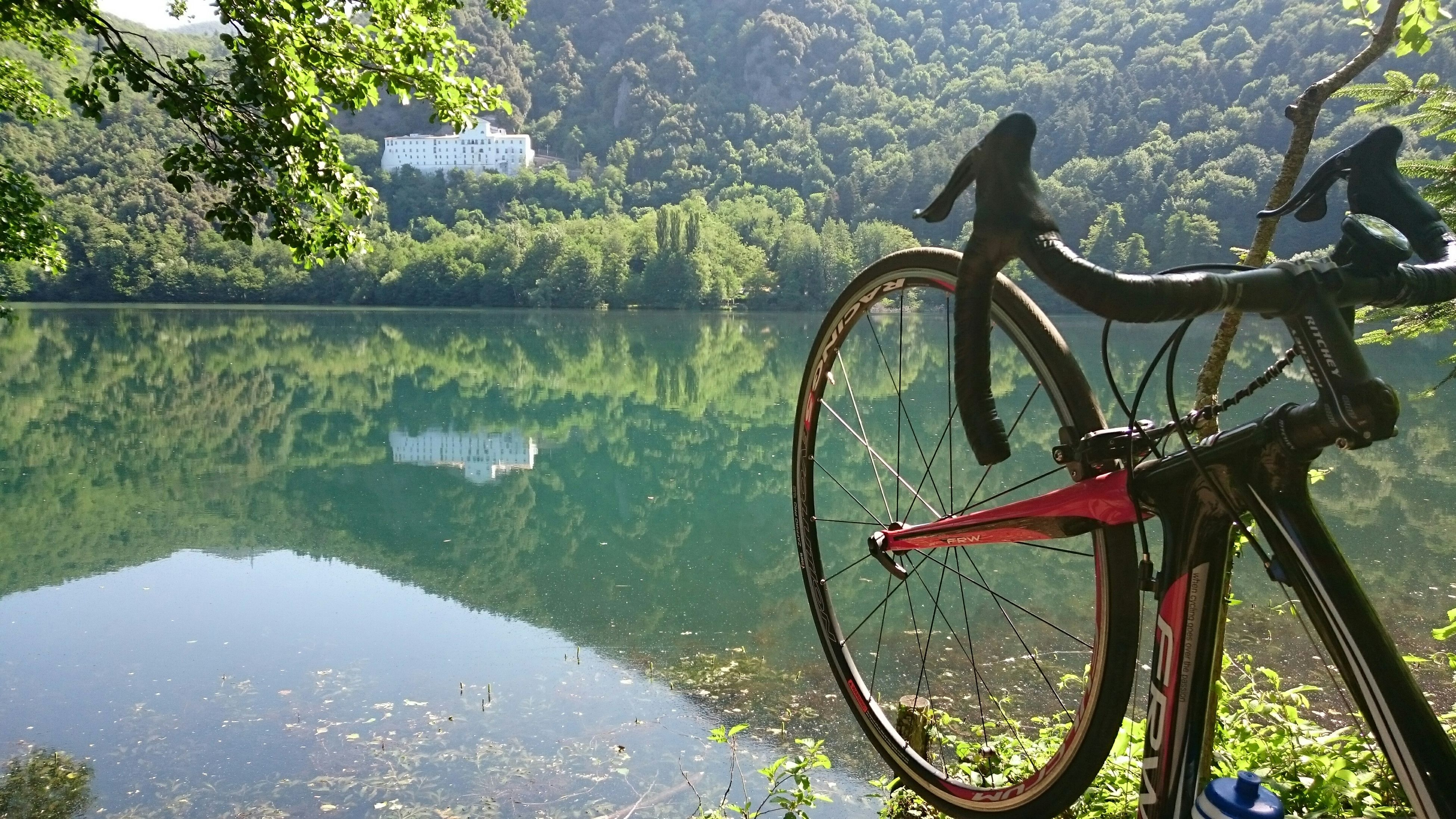 water, transportation, mode of transport, bicycle, river, lake, tree, land vehicle, tranquility, nature, nautical vessel, boat, beauty in nature, tranquil scene, plant, reflection, stationary, day, growth, no people