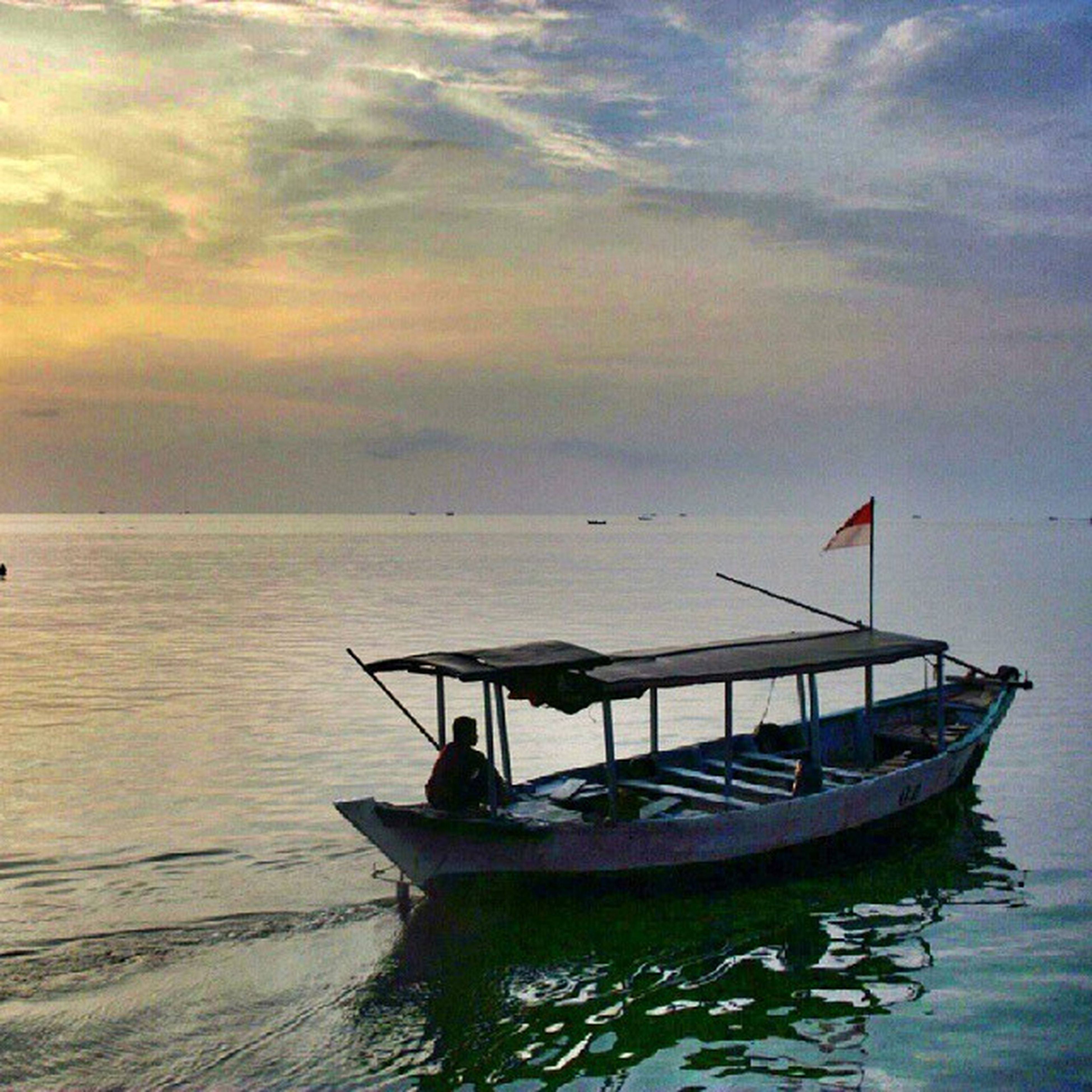 water, nautical vessel, sea, boat, transportation, sky, waterfront, mode of transport, horizon over water, tranquil scene, tranquility, cloud - sky, scenics, beauty in nature, sunset, nature, moored, cloud, rippled, cloudy