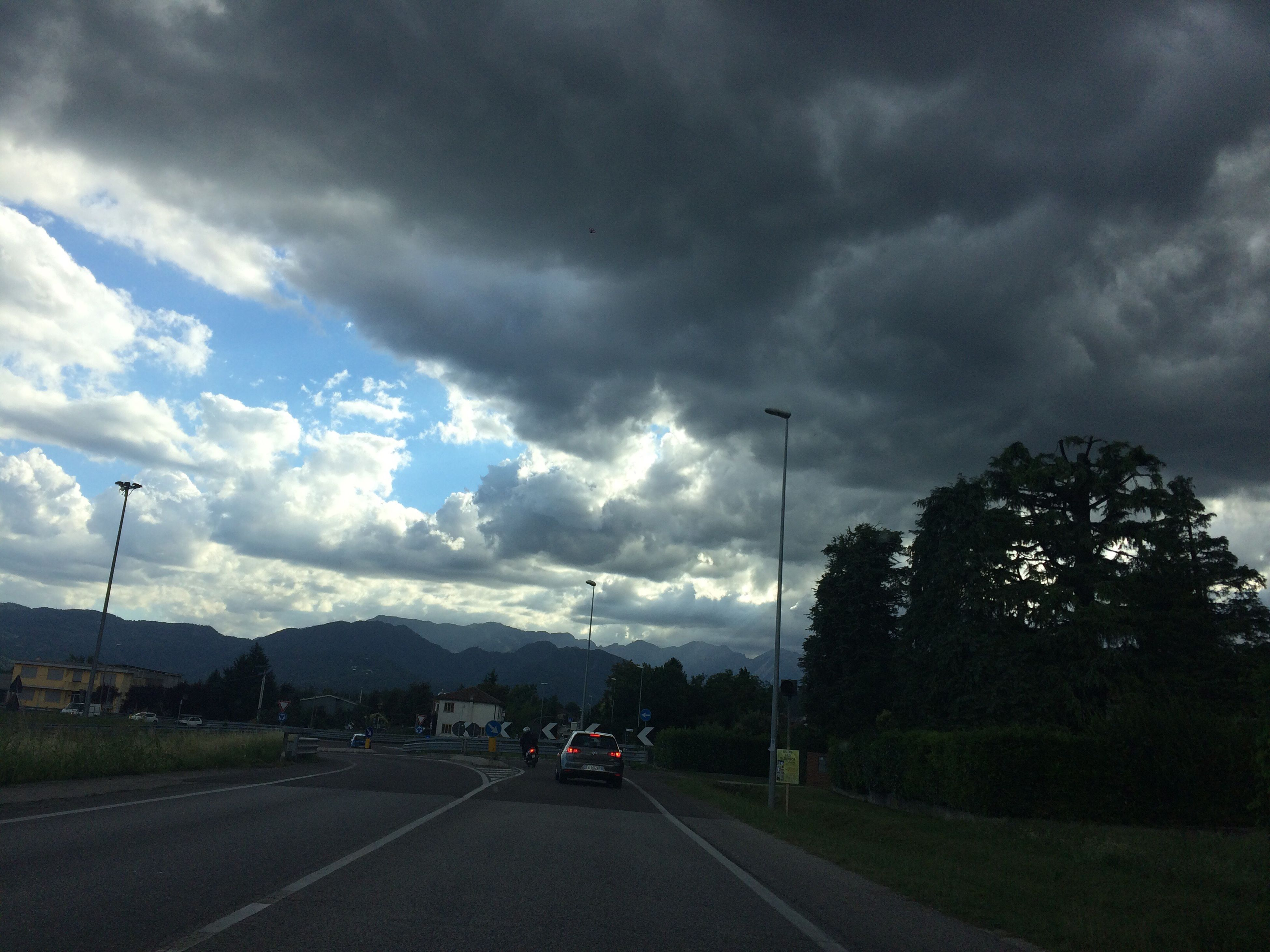 car, road, cloud - sky, transportation, sky, land vehicle, dramatic sky, storm cloud, street light, tree, outdoors, the way forward, day, no people, mountain, nature, thunderstorm, beauty in nature