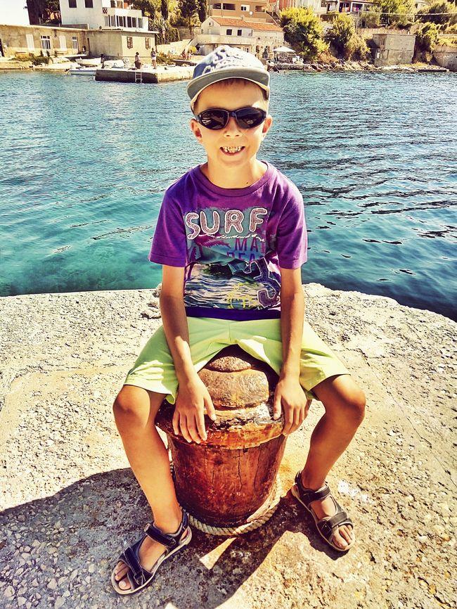 Boy sitting on a mooring bollard in Savar, Dugi Otok island, Croatia Boy MooringBollards Sitting Savar Dugiotok Travel Summer Vacation Croatia Adriatic Sea