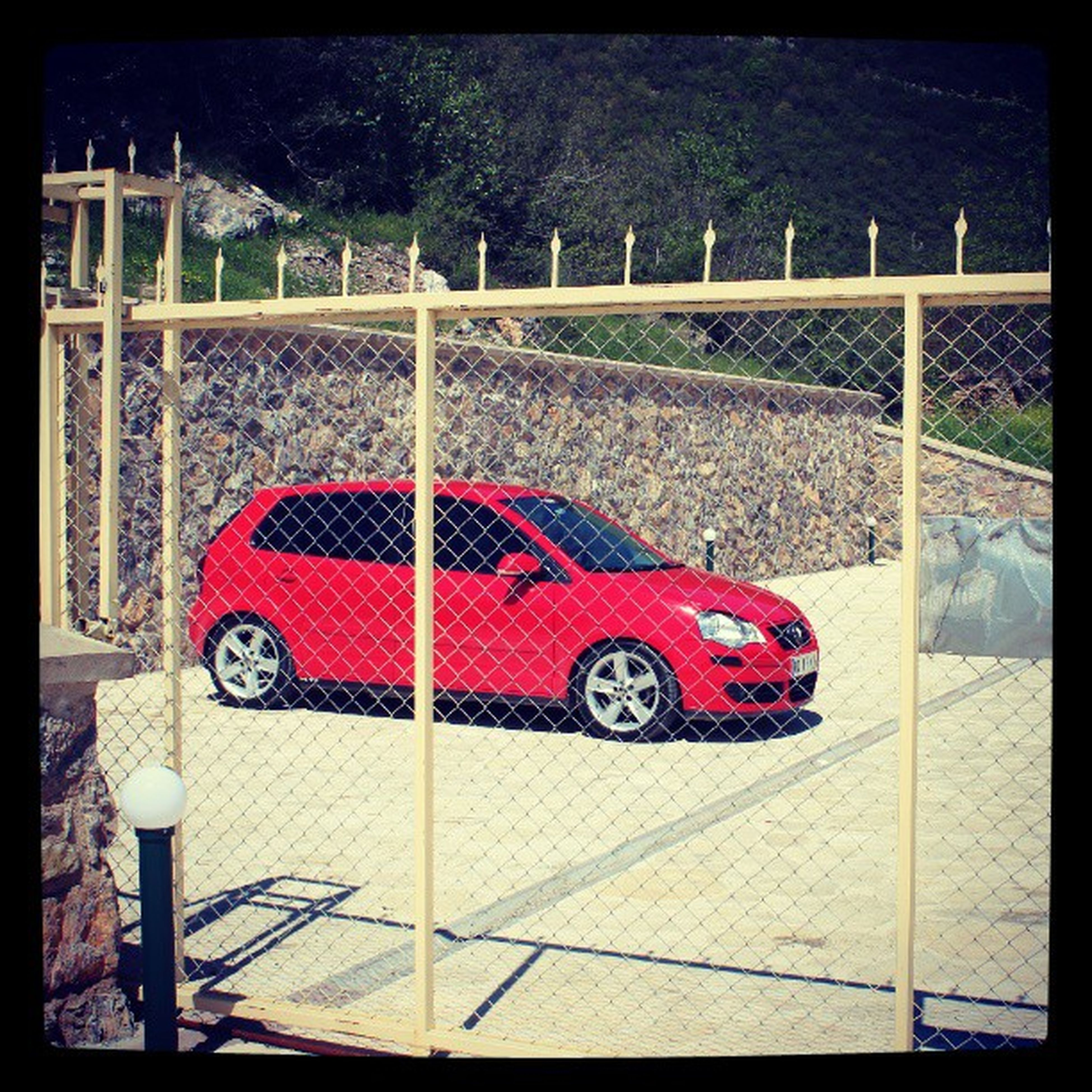 transfer print, auto post production filter, red, fence, transportation, railing, protection, metal, safety, day, gate, tree, outdoors, sunlight, built structure, playground, street, no people, land vehicle, chainlink fence