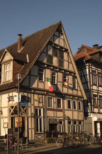 Oldest Pizzaria in Town Apartment Architectural Feature Architecture Bicycles Building Exterior Built Structure City City Life Clear Sky Day Development Façade Fasada Flags No People Old Town Outdoors Residential Building Residential Structure Restaurante Sky Street Corner The Way Forward