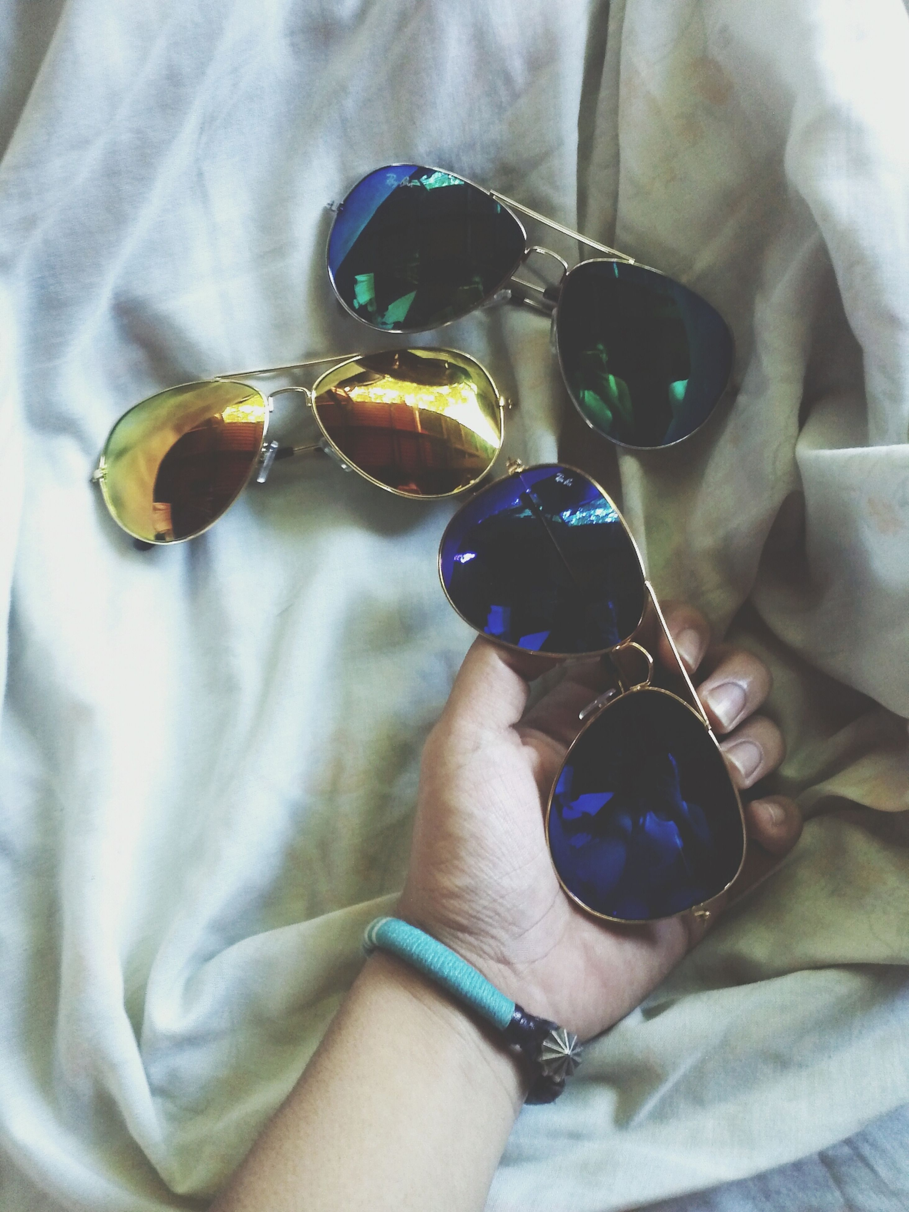 indoors, lifestyles, person, leisure activity, holding, part of, fashion, close-up, unrecognizable person, jewelry, high angle view, sunglasses, personal perspective, men, human finger, cropped