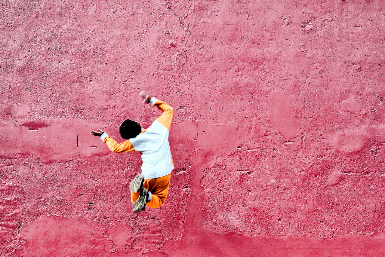Architecture Background Boy Alone Boy Jumping Day Full Length One Person Outdoors Pink Color Victory Pink Wall Red Wall