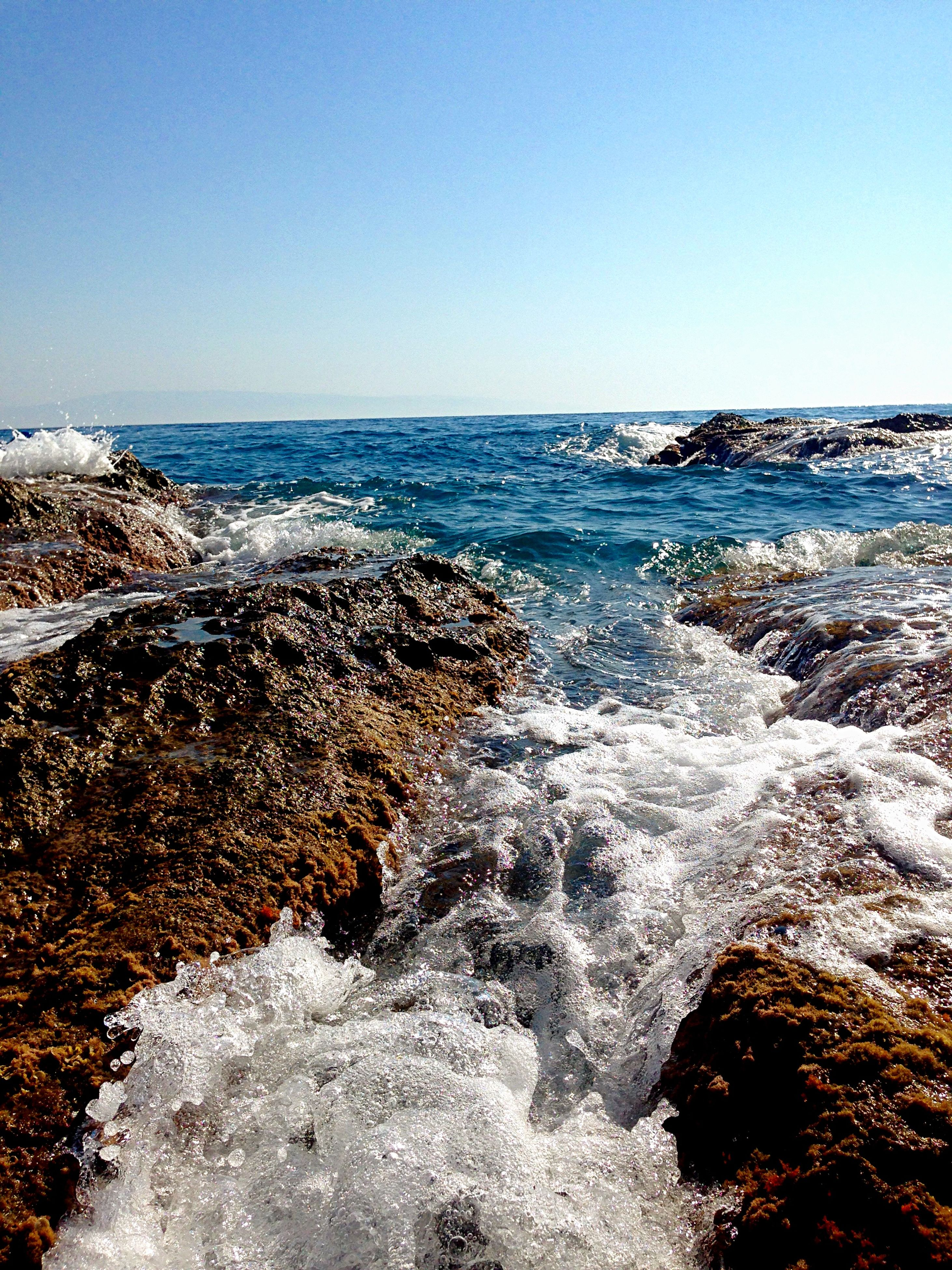 water, clear sky, sea, scenics, copy space, surf, beauty in nature, horizon over water, wave, beach, tranquil scene, nature, shore, blue, tranquility, motion, rock - object, idyllic, sky, day