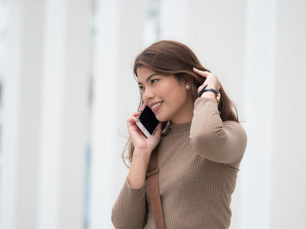 Answering Business Business Finance And Industry Businesswoman Communication Connection Happiness Holding Indoors  Listening Mobile Phone One Person One Woman Only One Young Woman Only Portable Information Device Smart Phone Smiling Talking Technology Telephone Using Phone Wireless Technology Women Young Adult Young Women
