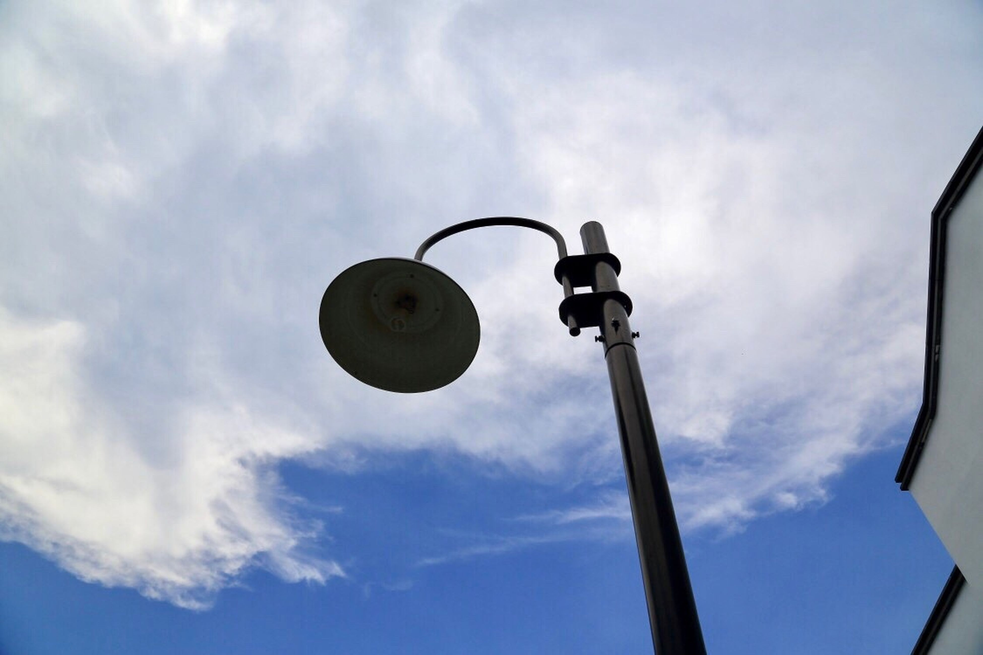 low angle view, sky, cloud - sky, street light, lighting equipment, communication, outdoors, no people, day, signal, road sign, architecture
