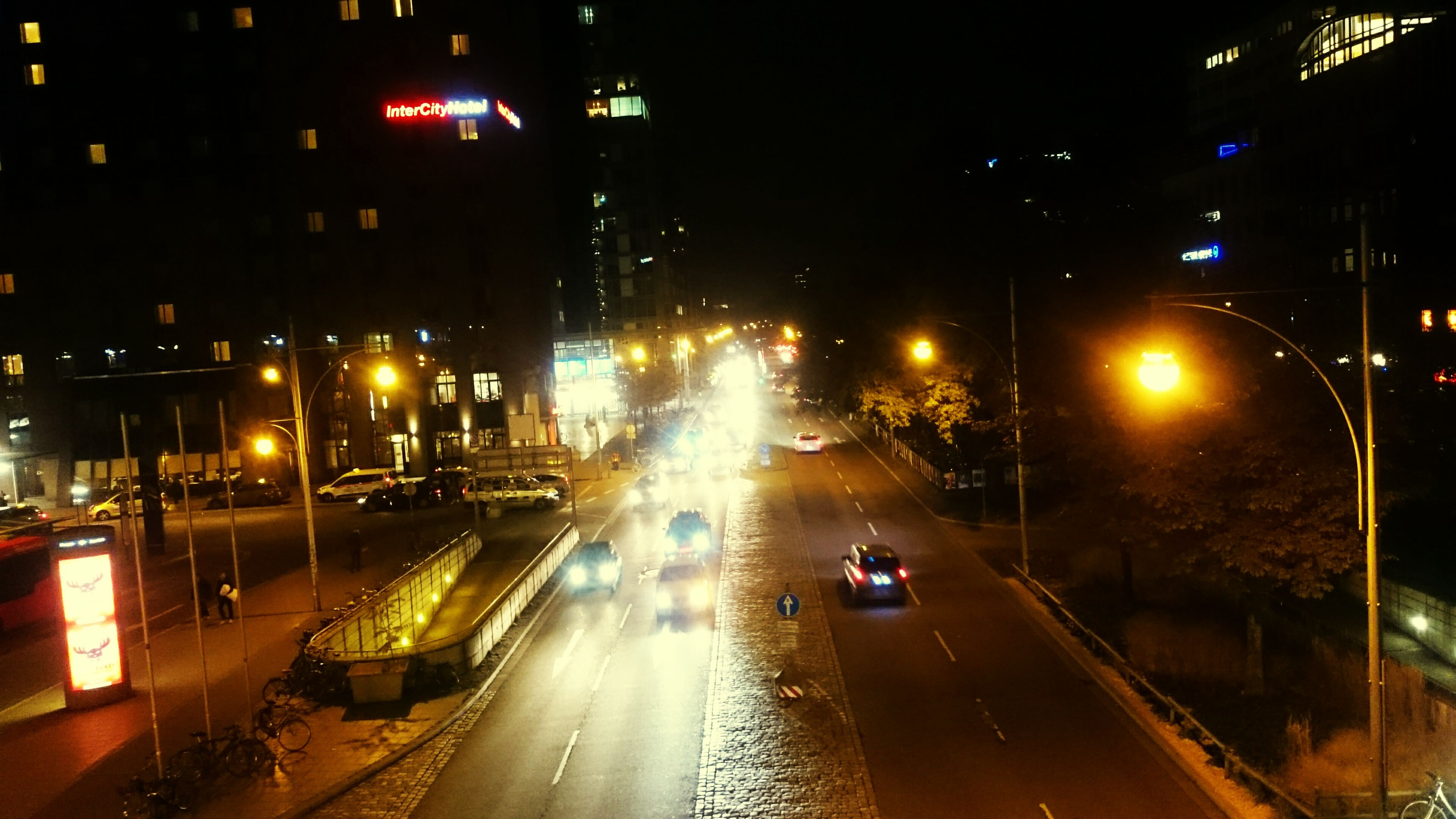 transportation, illuminated, night, car, city, mode of transport, land vehicle, building exterior, street, street light, traffic, architecture, built structure, road, city street, city life, on the move, high angle view, the way forward, wet