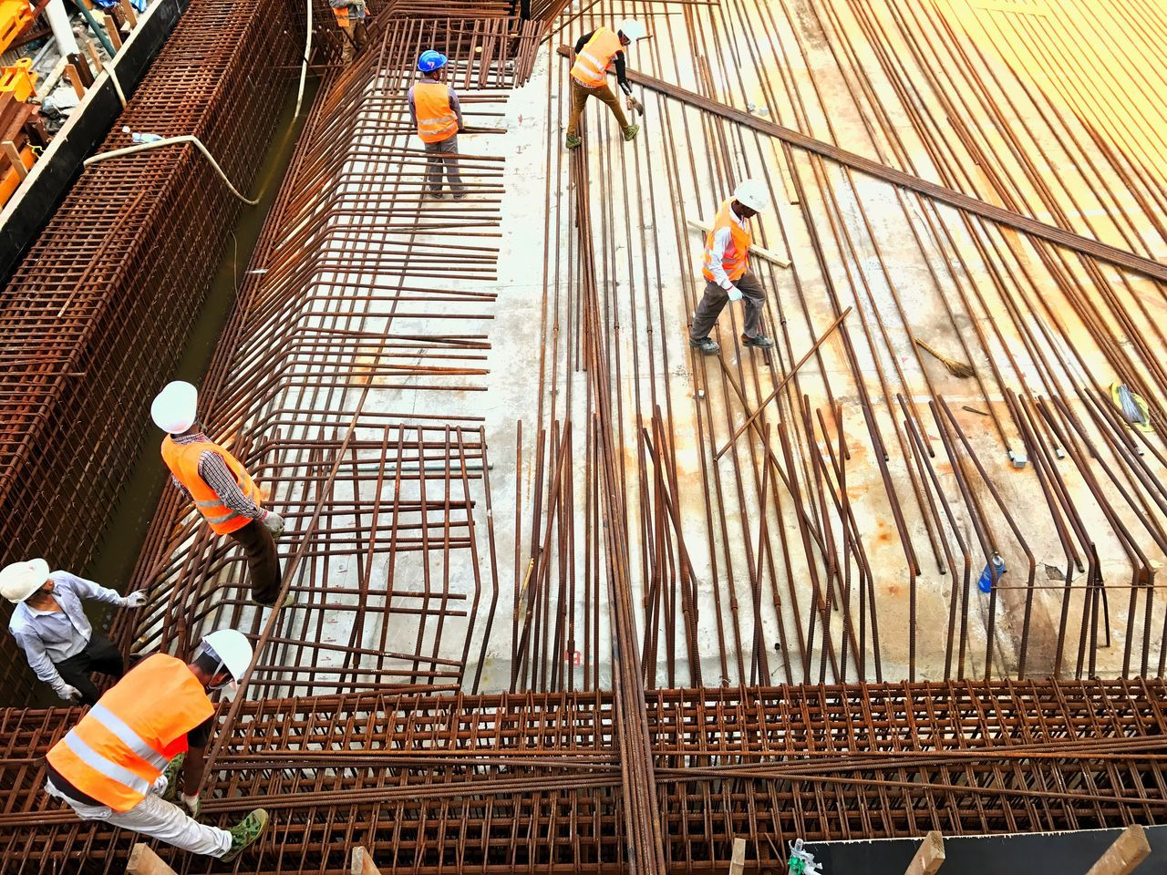 Workers at construction site Metalwork Construction Civil Rngineering Headwear Manual Worker Helmet Togetherness Teamwork Outdoors Industry Ground Concrete Cement Iron Bar Barbender Construction Site