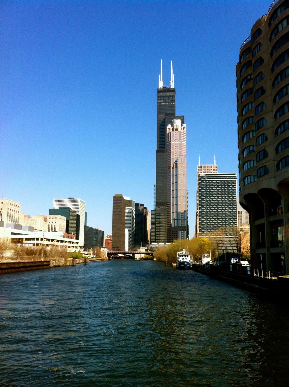 River Amidst Modern Buildings Against Clear Blue Sky