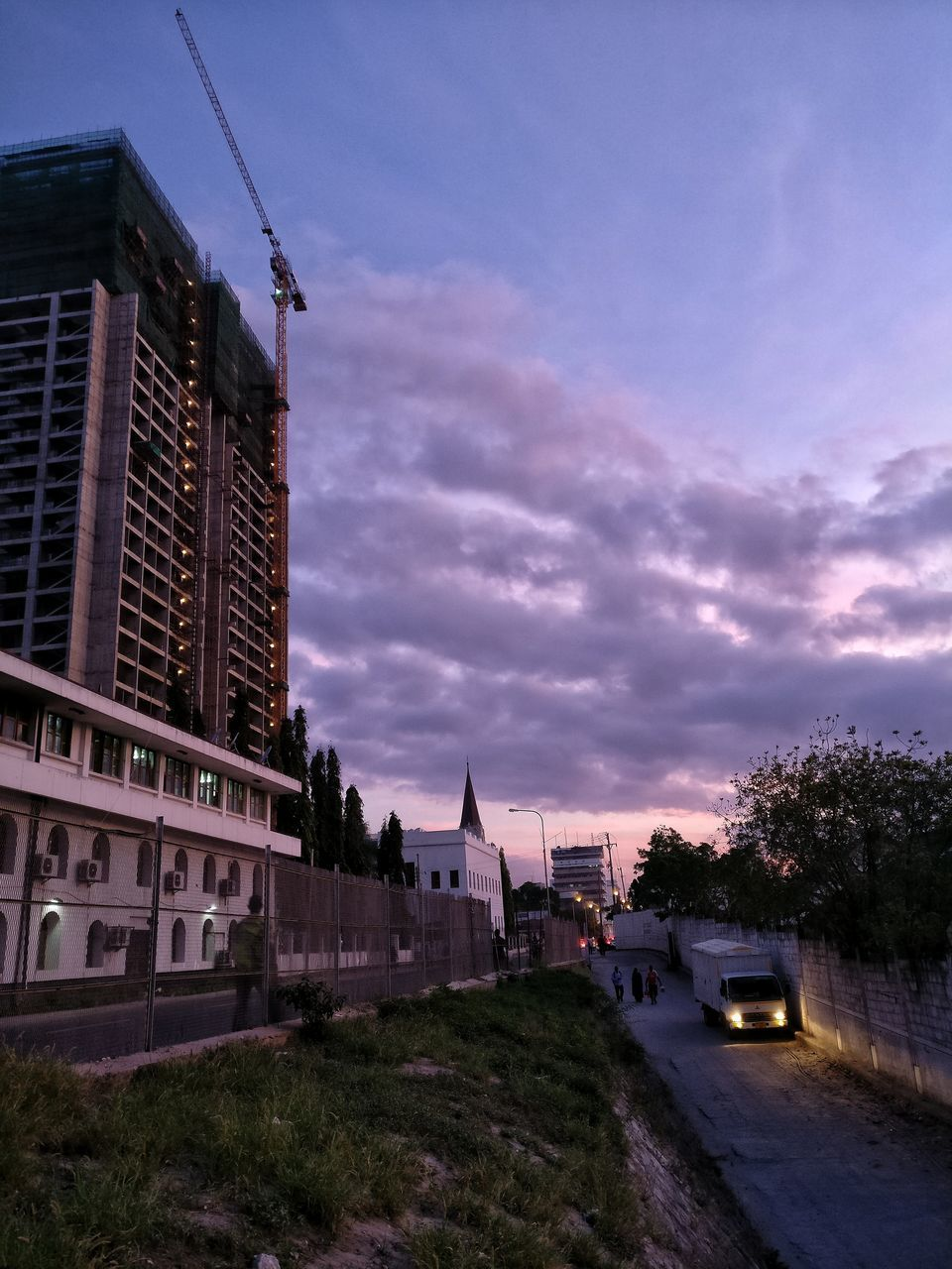 architecture, building exterior, built structure, car, transportation, land vehicle, sky, sunset, city, outdoors, mode of transport, no people, cloud - sky, residential building, tree, road, nature, day