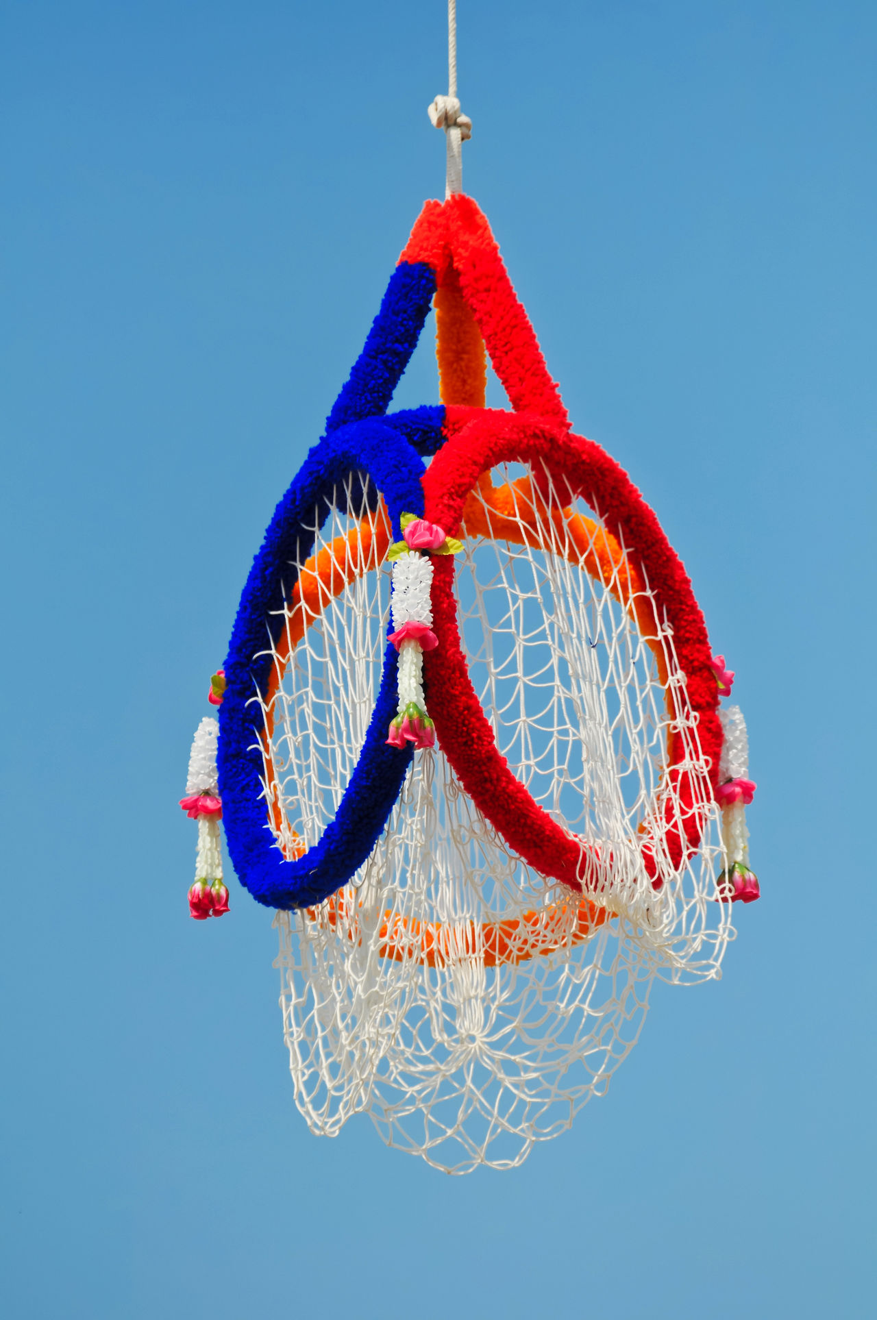 Thai sports known as Takraw through hoops Above Asian Culture Blue Sky Day Game High Kick Leisure Activity Loop Net No People Outdoors Red Color Skill  Sky Sling Southeast Asia Sphere Striped Takraw Thailand..