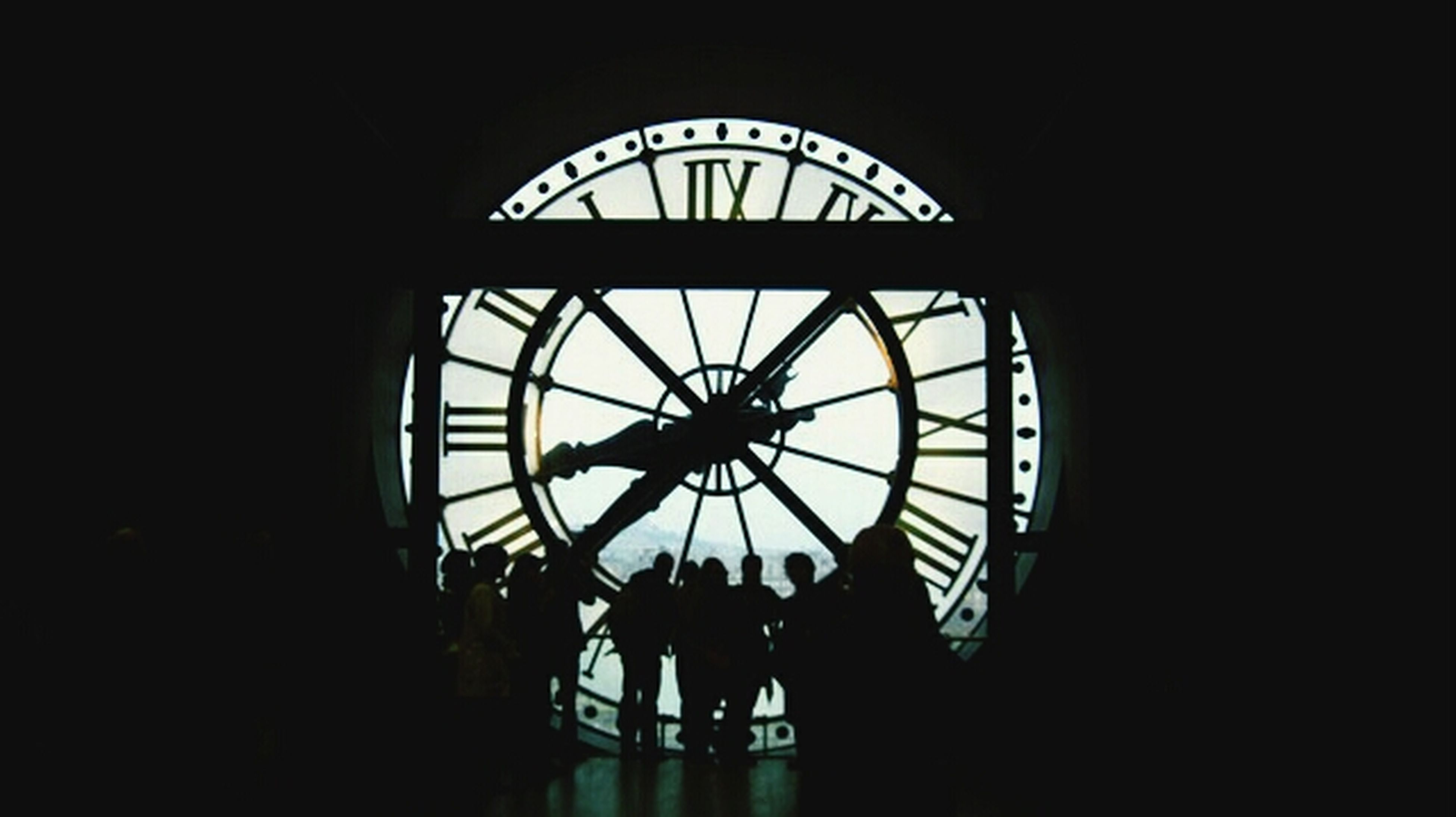 indoors, silhouette, built structure, low angle view, architecture, circle, clock, window, geometric shape, time, glass - material, sky, skylight, copy space, dark, clear sky, day, directly below, ceiling, shape