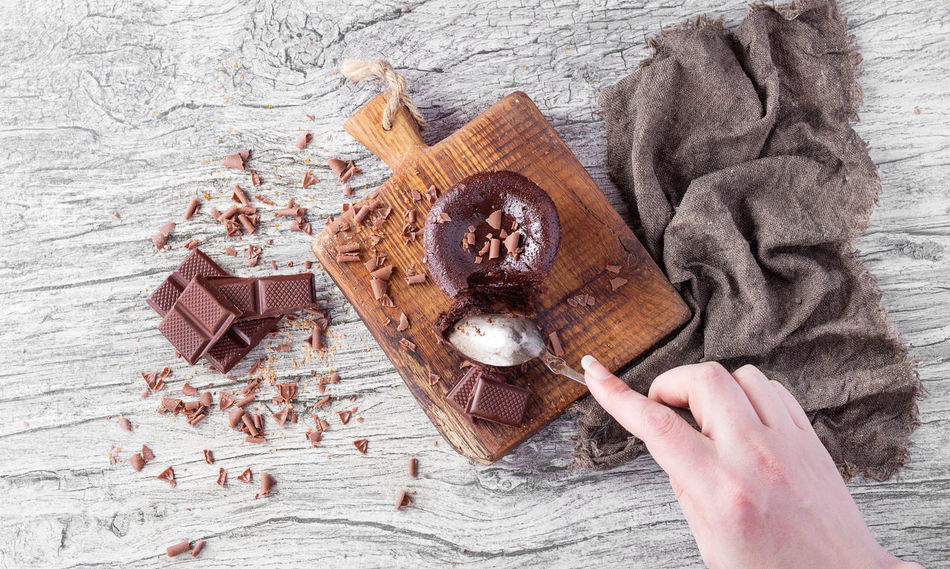 Homemade chocolate fondant served on rustic wooden board with chocolate chips and cubes decorated with grey napkin. Top view Background Bars Cake Chips Chocolate Fondant  Food Grey Napkin Souffle Spoon Top View Wooden
