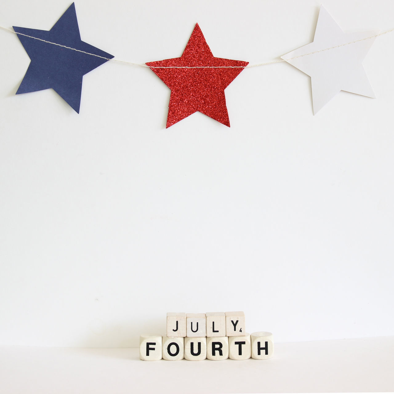 July And Fourth Blocks On Table Against Wall With Decoration