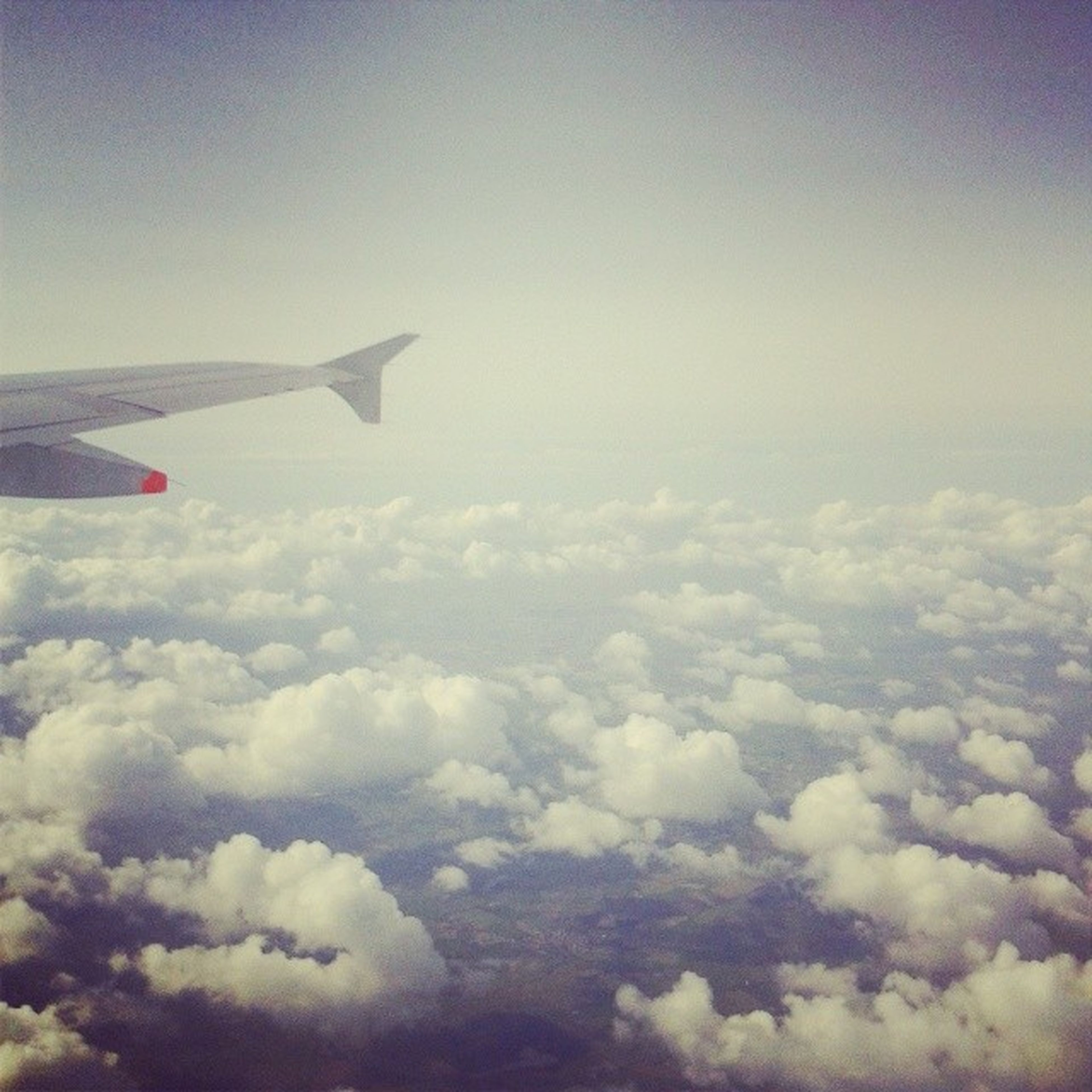 airplane, flying, air vehicle, aircraft wing, transportation, mode of transport, mid-air, sky, part of, cropped, aerial view, cloud - sky, travel, cloudscape, journey, on the move, blue, nature, beauty in nature, cloud