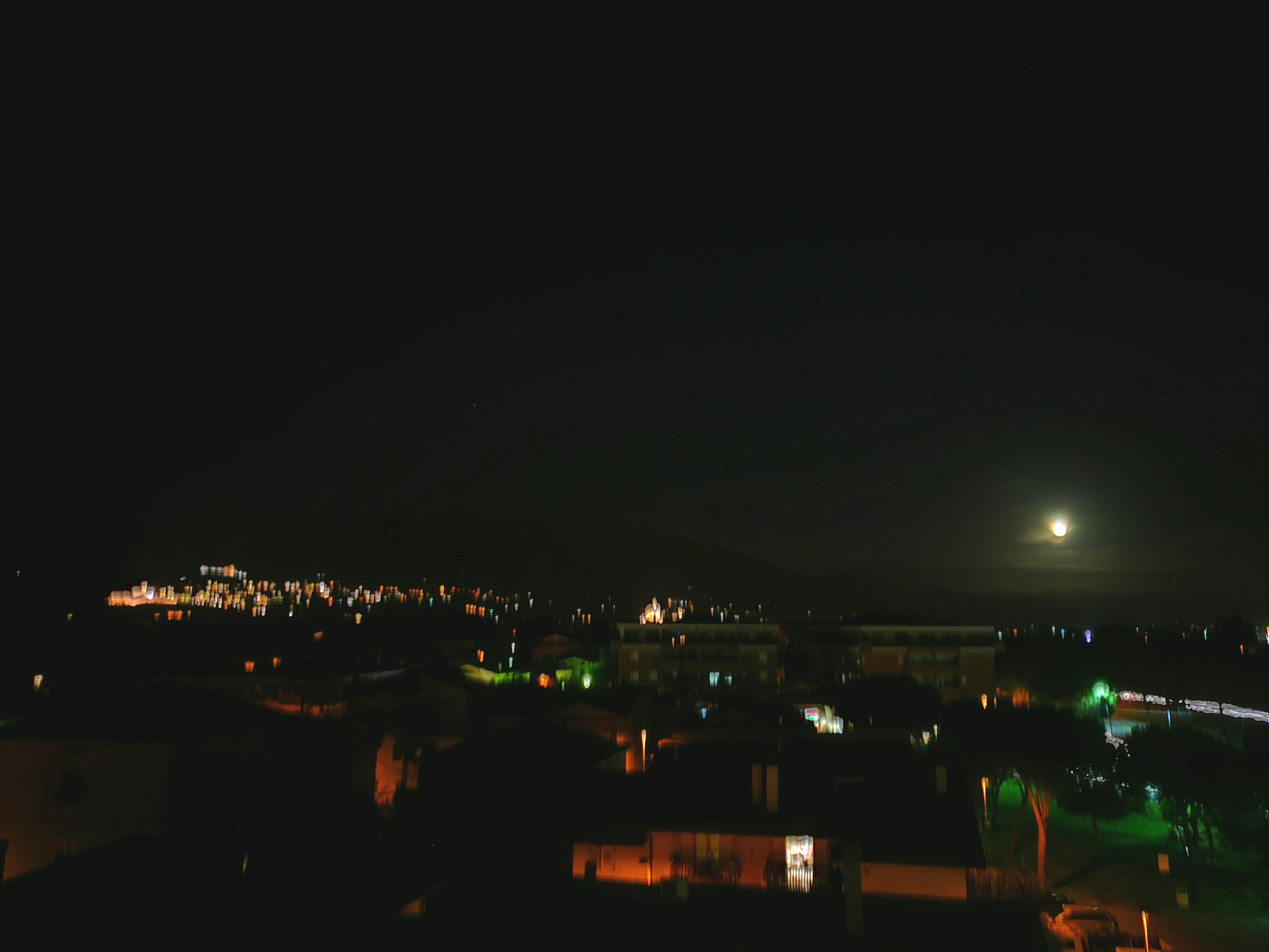 night, illuminated, building exterior, built structure, architecture, city, cityscape, dark, copy space, high angle view, sky, residential structure, residential building, residential district, clear sky, crowded, house, outdoors, city life, moon