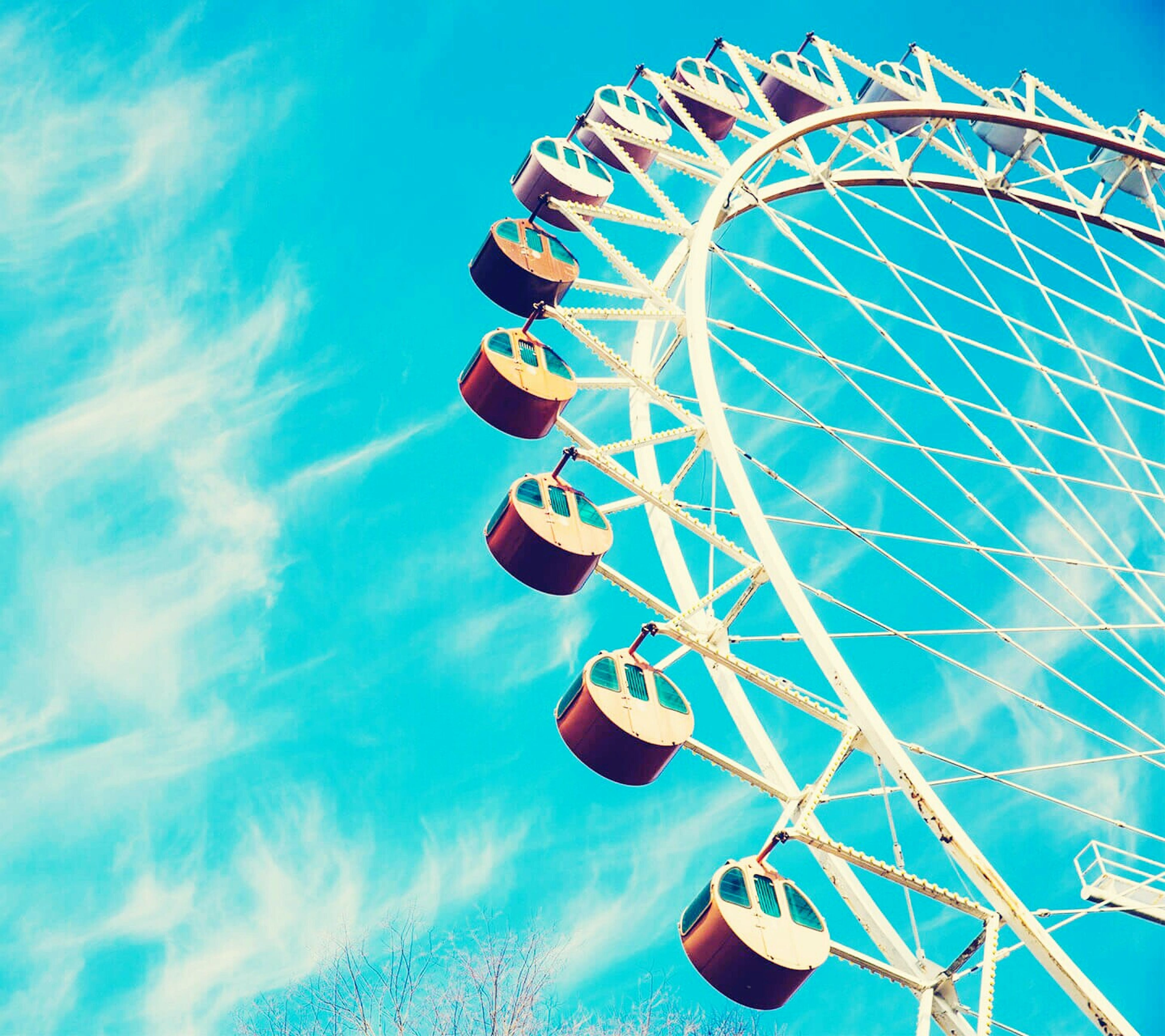 amusement park, low angle view, amusement park ride, ferris wheel, arts culture and entertainment, blue, sky, fun, enjoyment, outdoors, day, chain swing ride, multi colored, cloud - sky, circle, no people, leisure activity, metal, fairground ride, pattern