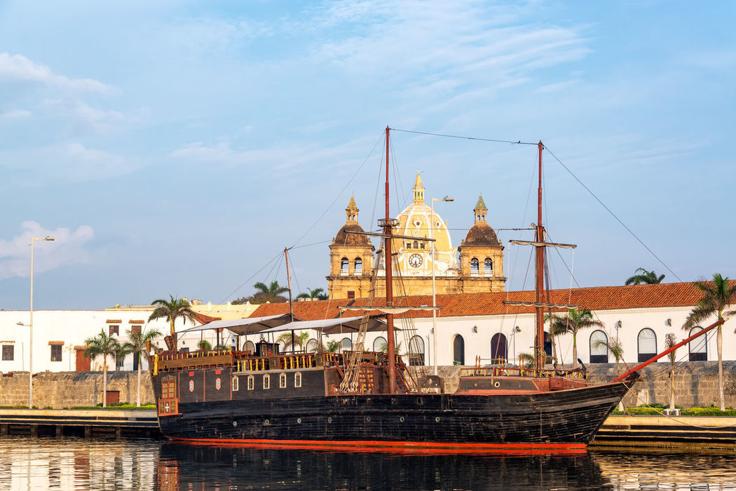 View of an old style pirate ship with San Pedro Claver Church in the historic old city center in Cartagena, Colombia Boat Bolivar Buccaneer Caribbean Cartagena Center City Cityscape Colombia Colorful Convention Galleon Indias Monument Pirate Pirate Ship Ship Sight Sights Street Tourism UNESCO World Heritage Site Urban Water Waterfront