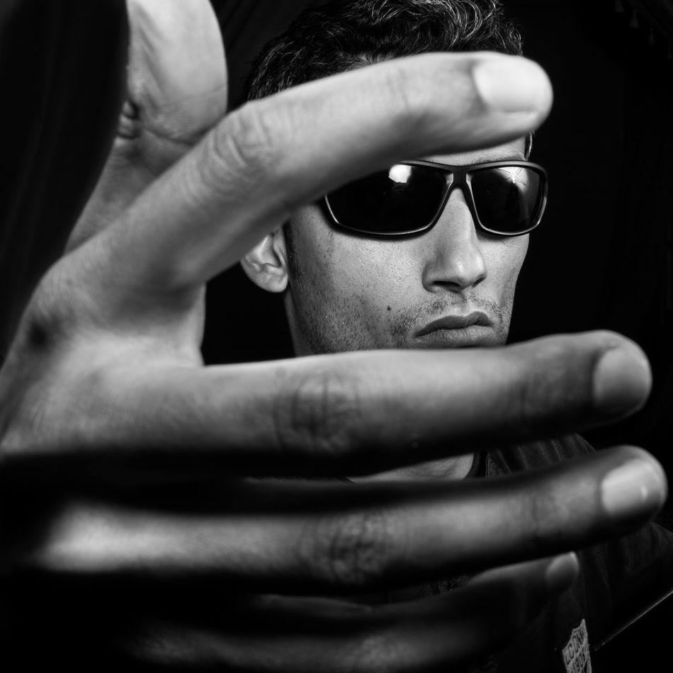 close-up of a hand hiding a man's face Black Black Background Close-up Day Headshot Human Face Human Hand Indoors  Lifestyles One Person People Real People Social Issues Studio Sunglasses Young Adult