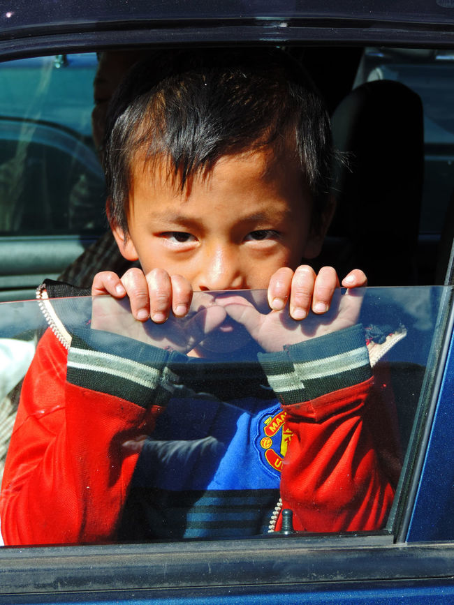 Boy in Bhutan peeking from car window ASIA Bhutan Boy Casual Clothing Child Close-up Cute Day Focus On Foreground Land Vehicle Leisure Activity Lifestyles Mode Of Transport Peek Peeking Portrait Sitting