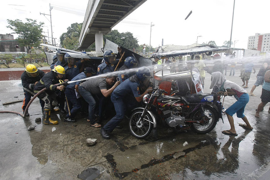 Anti riot police use water cannon to disperse a group of illegal settlers protesting the impending demolition of their homes in Quezon City Philippines, March 8, 2016. Informal settlers fight and would not leave their houses without relocation and they voice out that the action violated their rights to shelter. The Photojournalist - 2016 EyeEm Awards