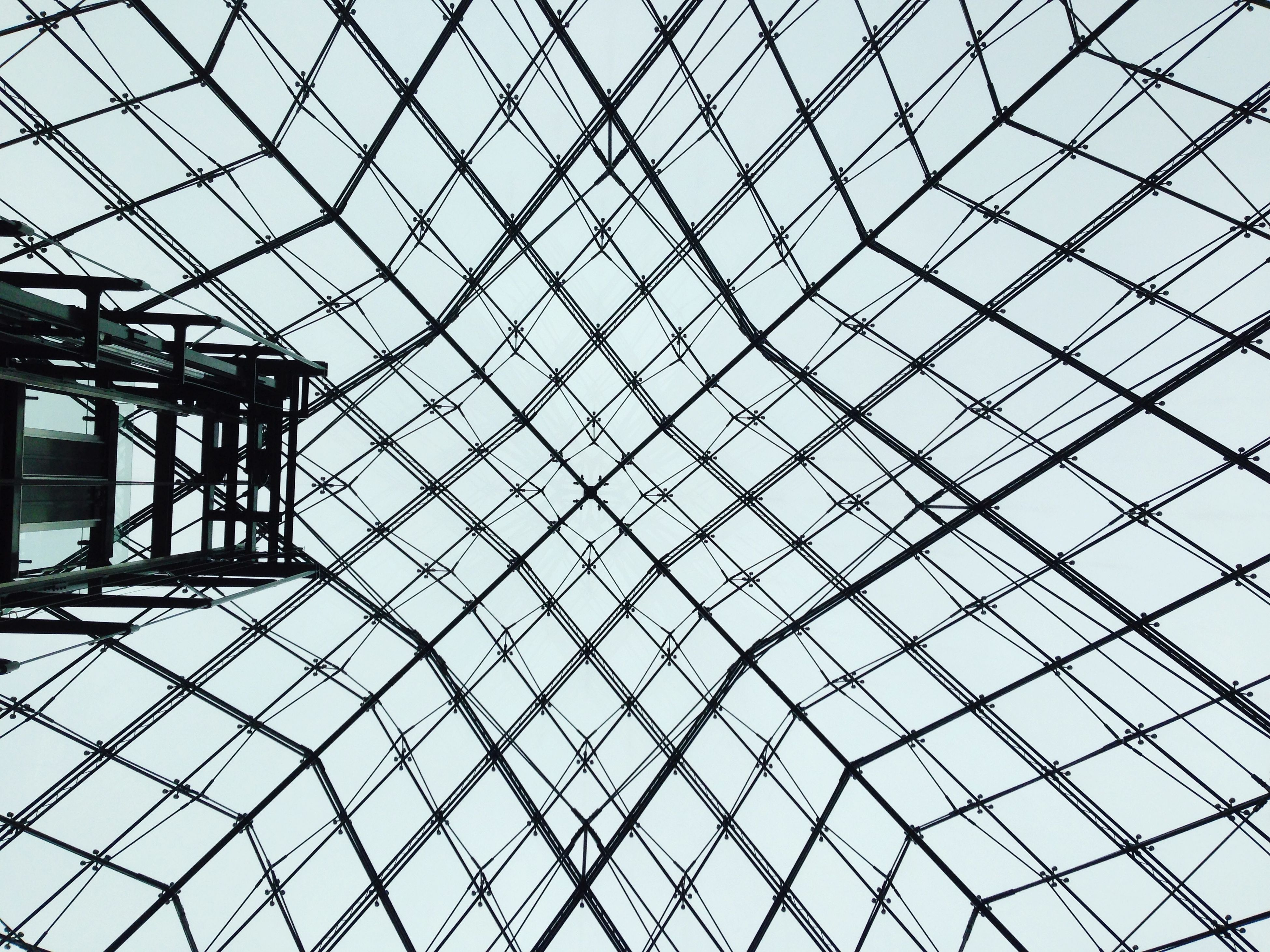 architecture, built structure, low angle view, glass - material, pattern, modern, ceiling, architectural feature, design, indoors, full frame, famous place, backgrounds, skylight, geometric shape, sky, building exterior, reflection, international landmark, travel destinations